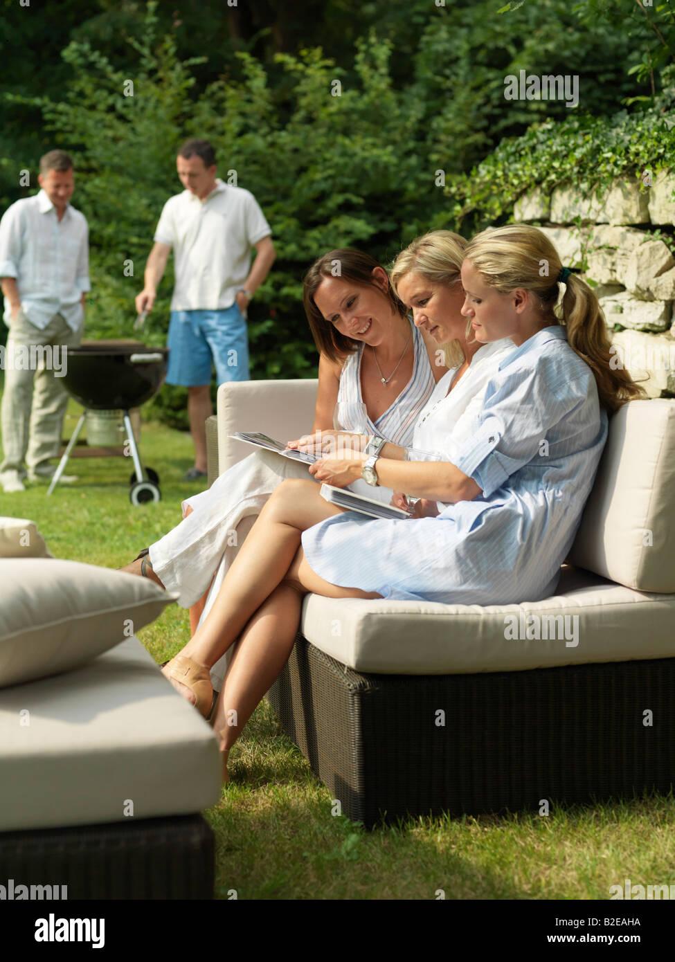 Drei Frauen betrachten Fotoalben auf couch Stockbild