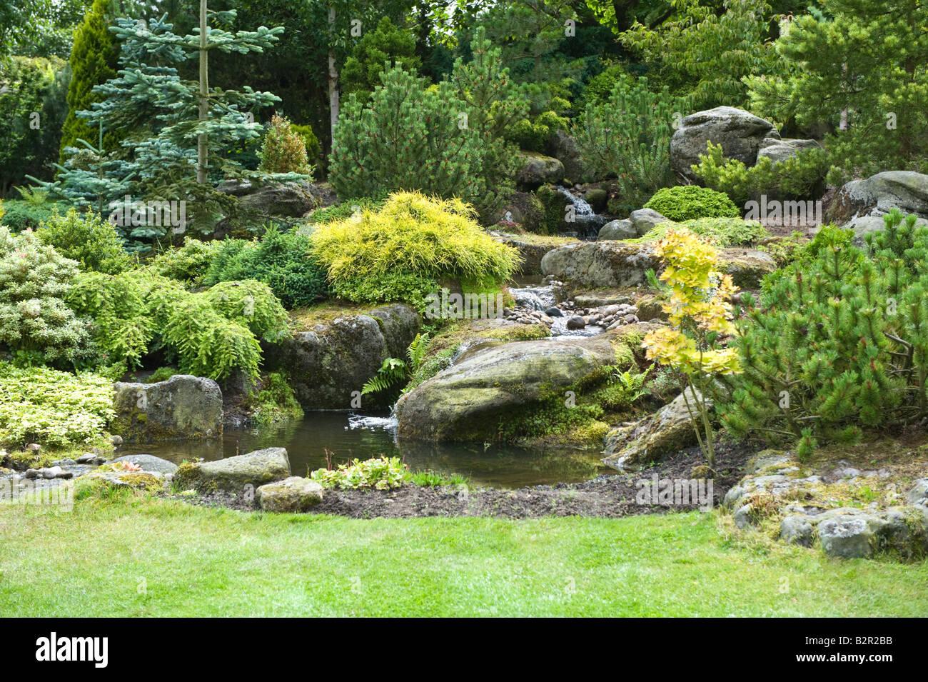 Steingarten mit Teich, Wasserfall, Sträuchern und Bäumen im Garten ...