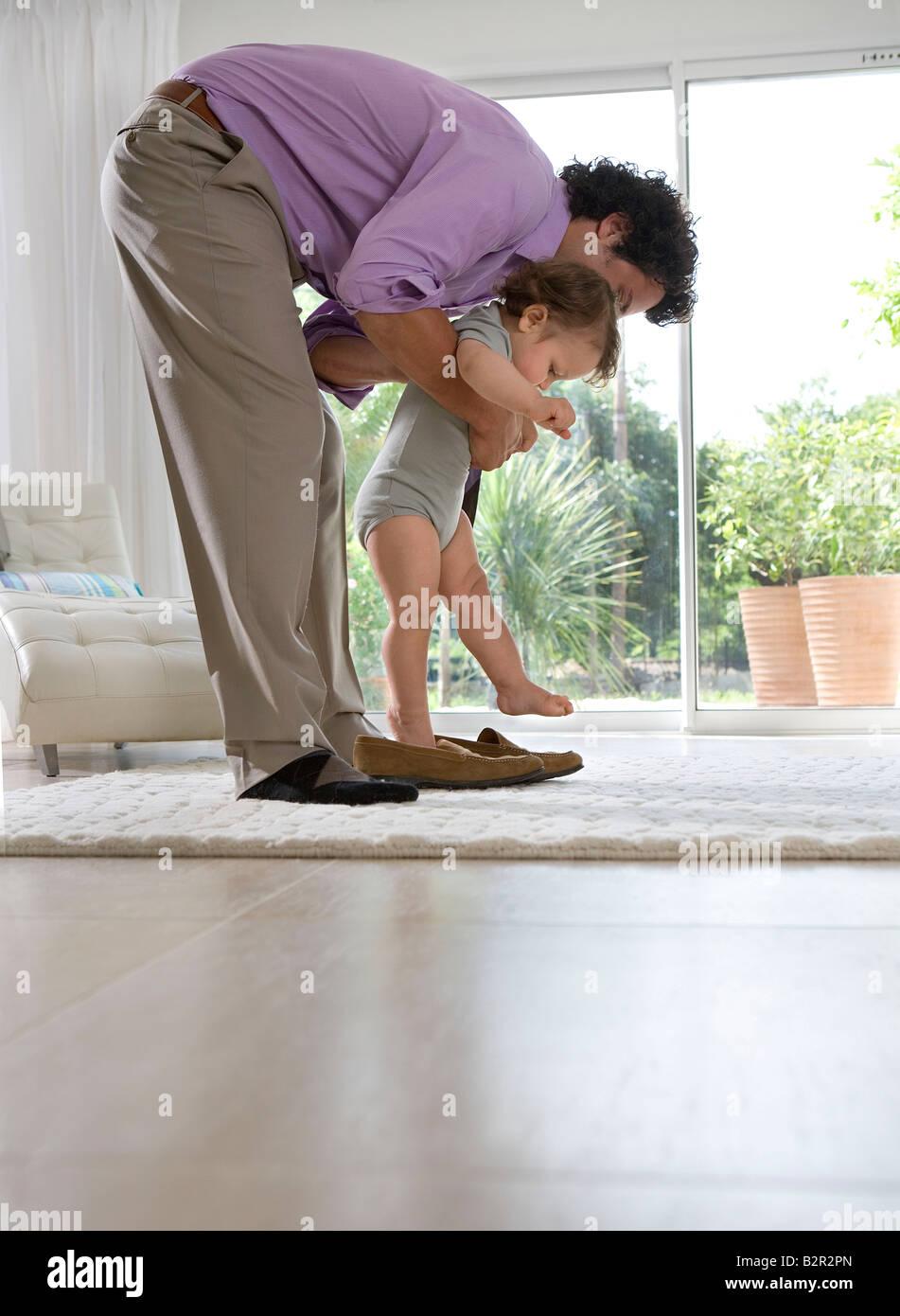 Vater bringt Baby Schuhe zu Hause Stockbild