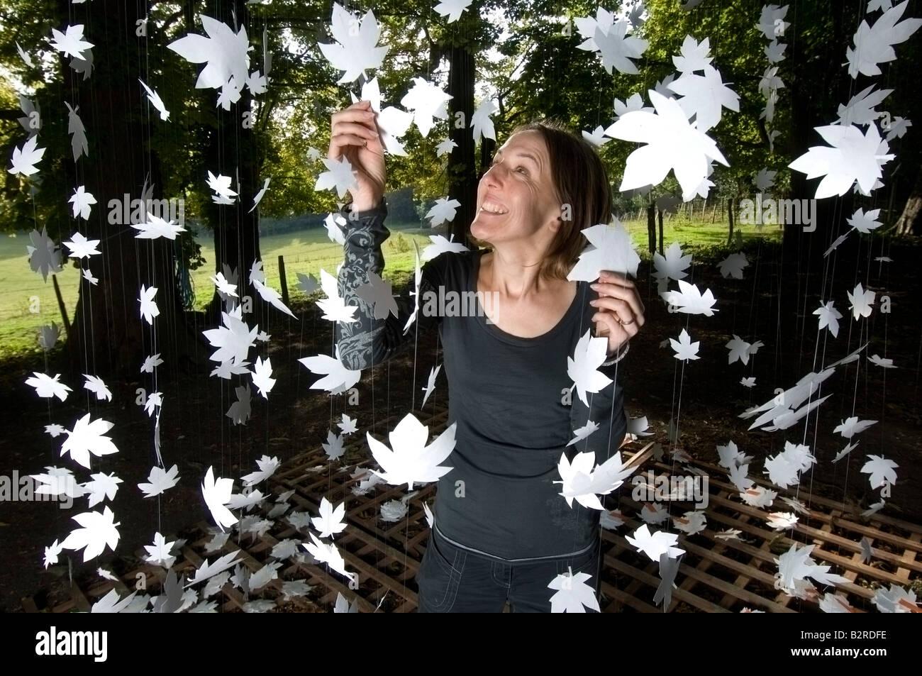 Eine Frau mit einem Vorhang aus Bergahorn Blattformen unter einem ...