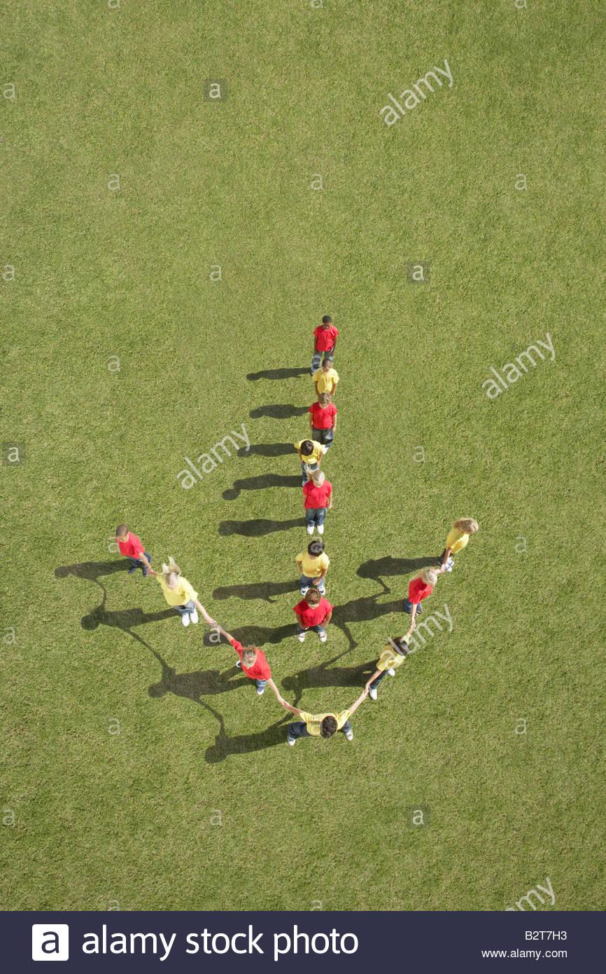 Gruppe von Kindern stehen in Pfeil-formation Stockbild