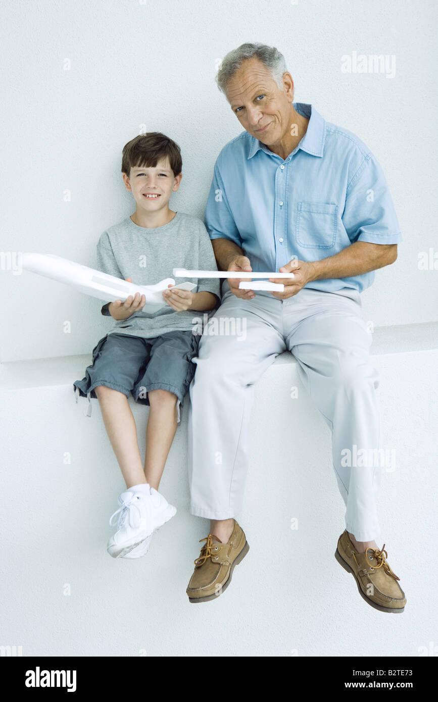 Großvater und Enkel sitzen nebeneinander, Holding-Modell Flugzeug Stücke, lächelnd in die Kamera Stockbild