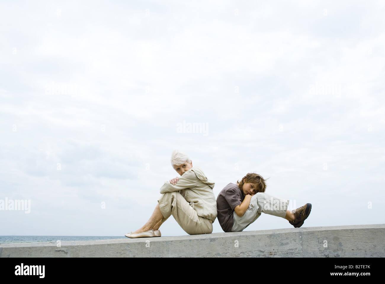 Großmutter und Enkel sitzen Rücken an Rücken, Arme verschränkt, junge Blick in die Kamera Stockbild