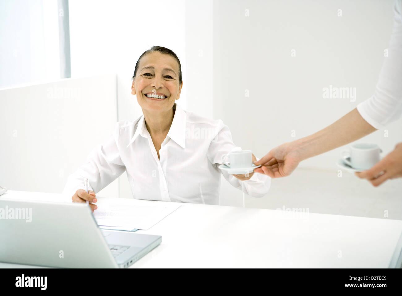 Senior Frau im Büro, Kaffee von Kollegen, lächelnd in die Kamera Stockbild
