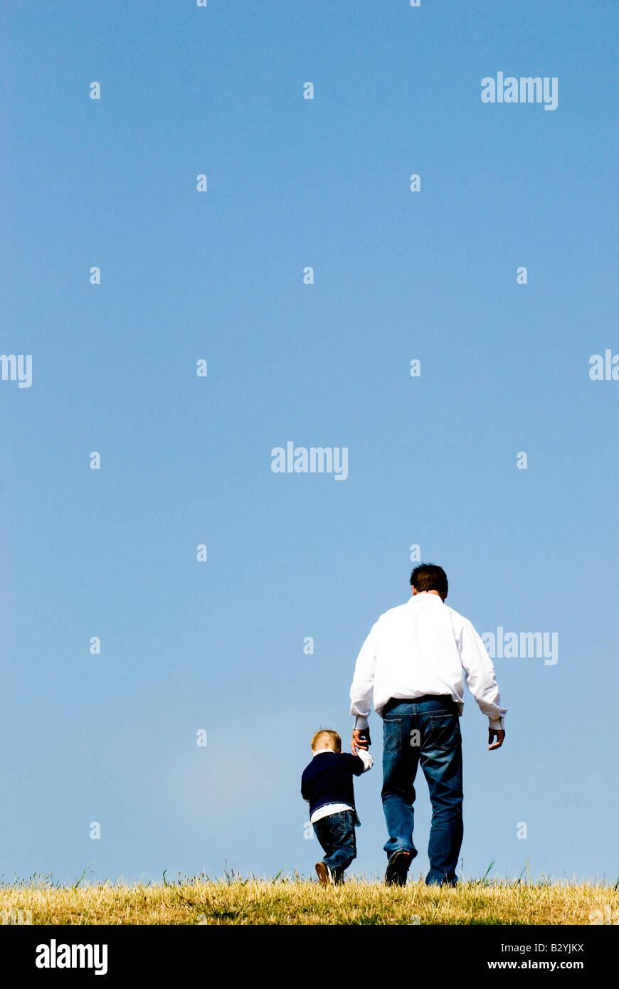 Vater und Sohn zu Fuß und Hand in Hand. Stockbild
