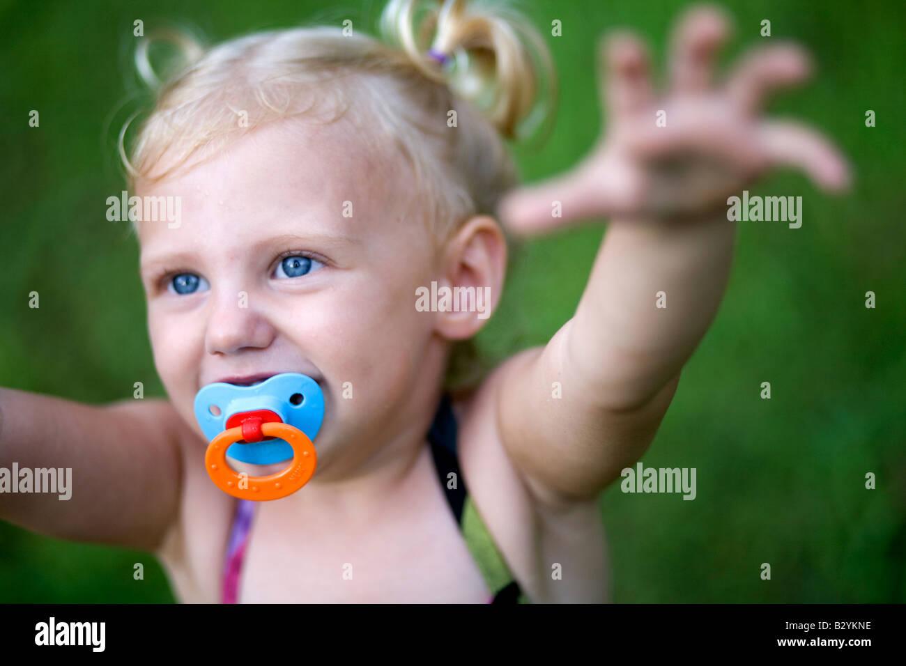 Ein zwei-jährigen Mädchen mit einem Schnuller und Pig Tails erreicht beim Spielen im Freien. Stockbild