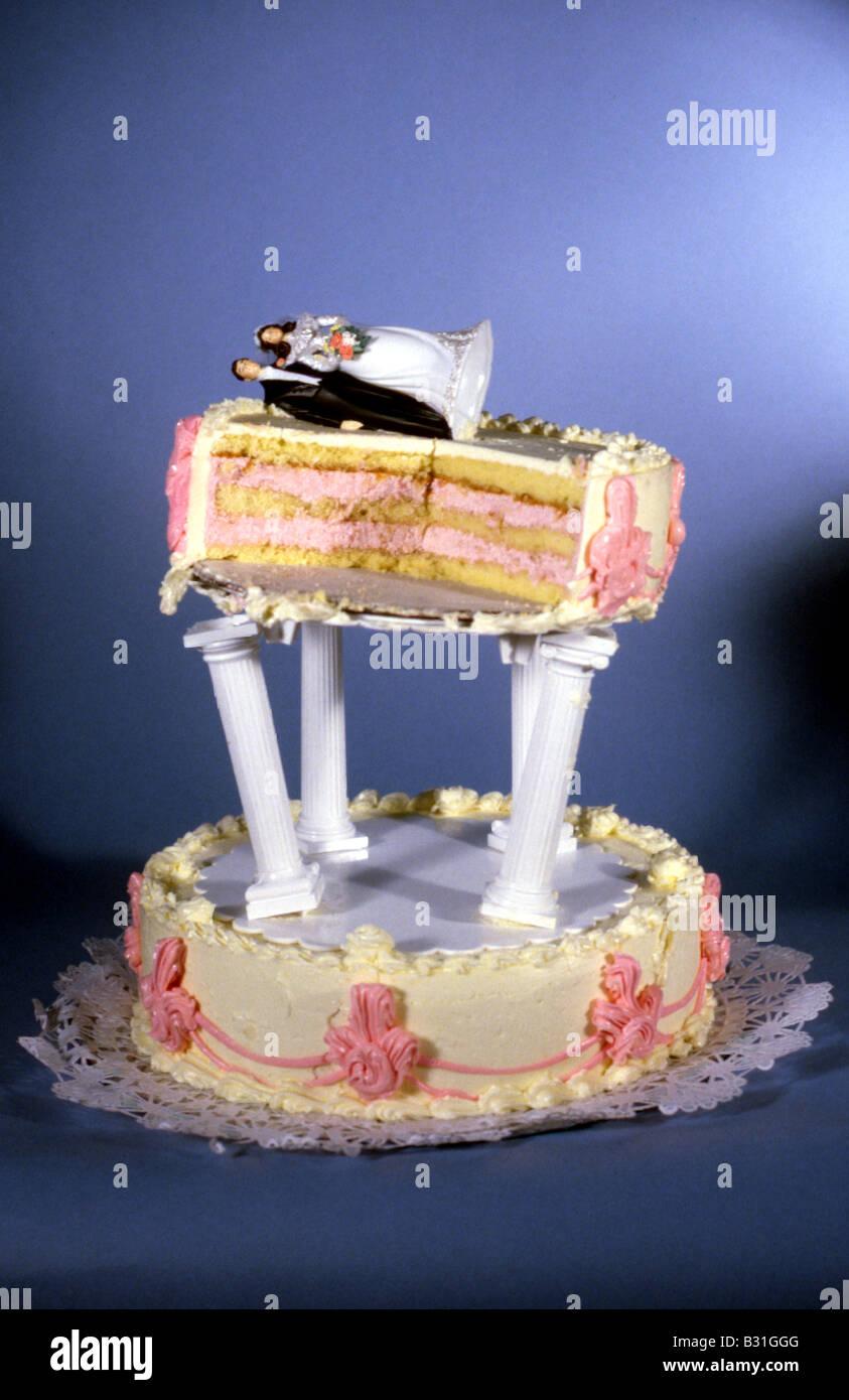 eine abgestufte Hochzeitstorte mit Kuchenstücke Ausschneiden und eine gestürzte Ornament der Braut und Stockbild
