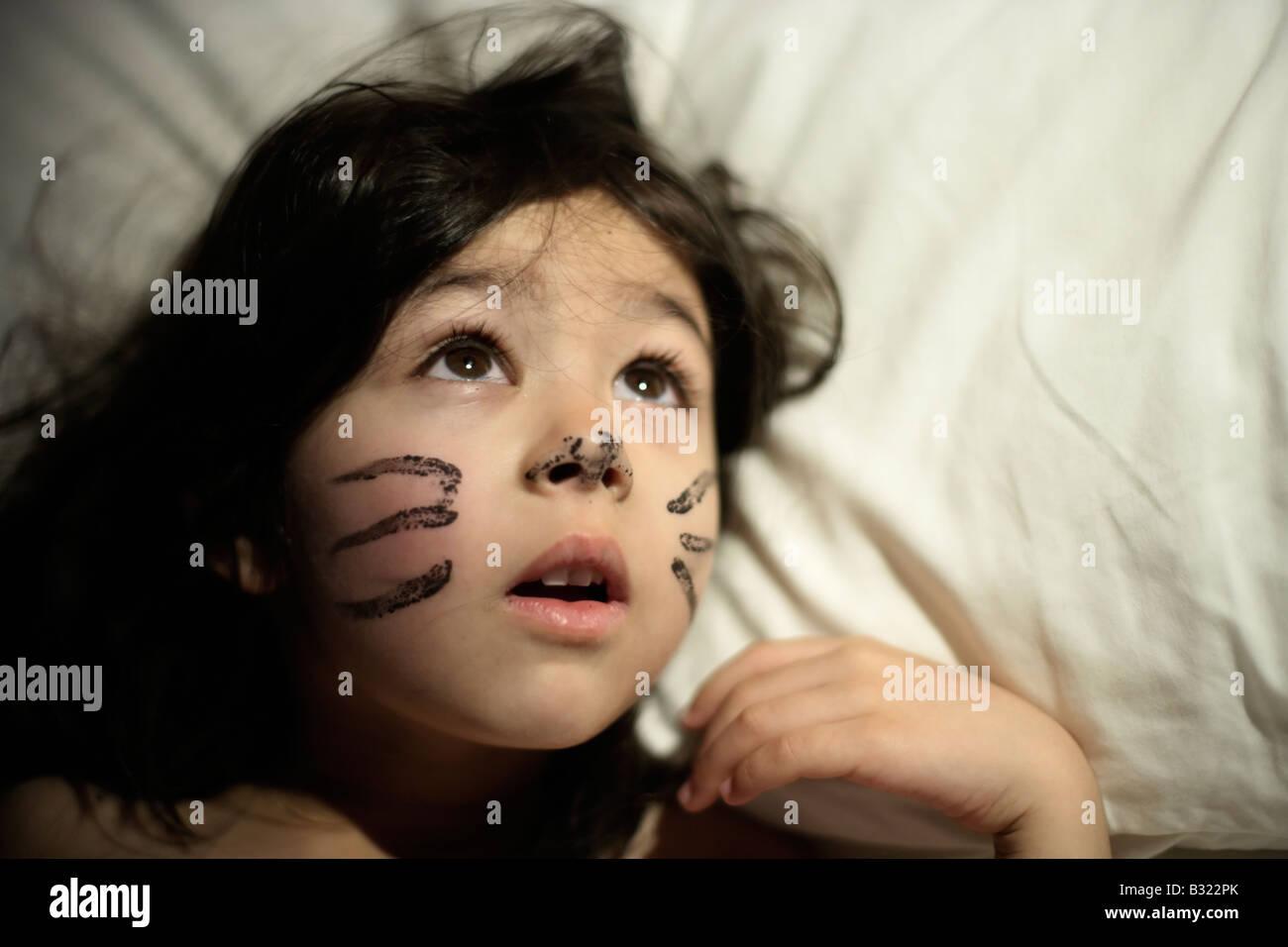 Fünf-Jahres-altes Mädchen mit des Vortages erwacht Gesicht malen. Sie spielte eine Katze in einer Schulaufführung Stockbild