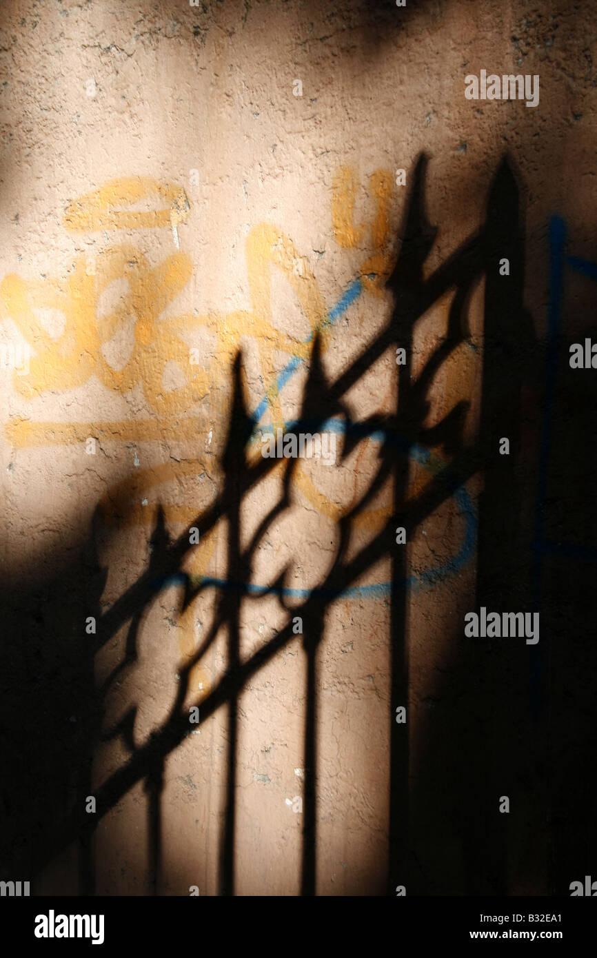 abstrakte Tor Zaun Schatten Graffitiwand im freien Stockbild