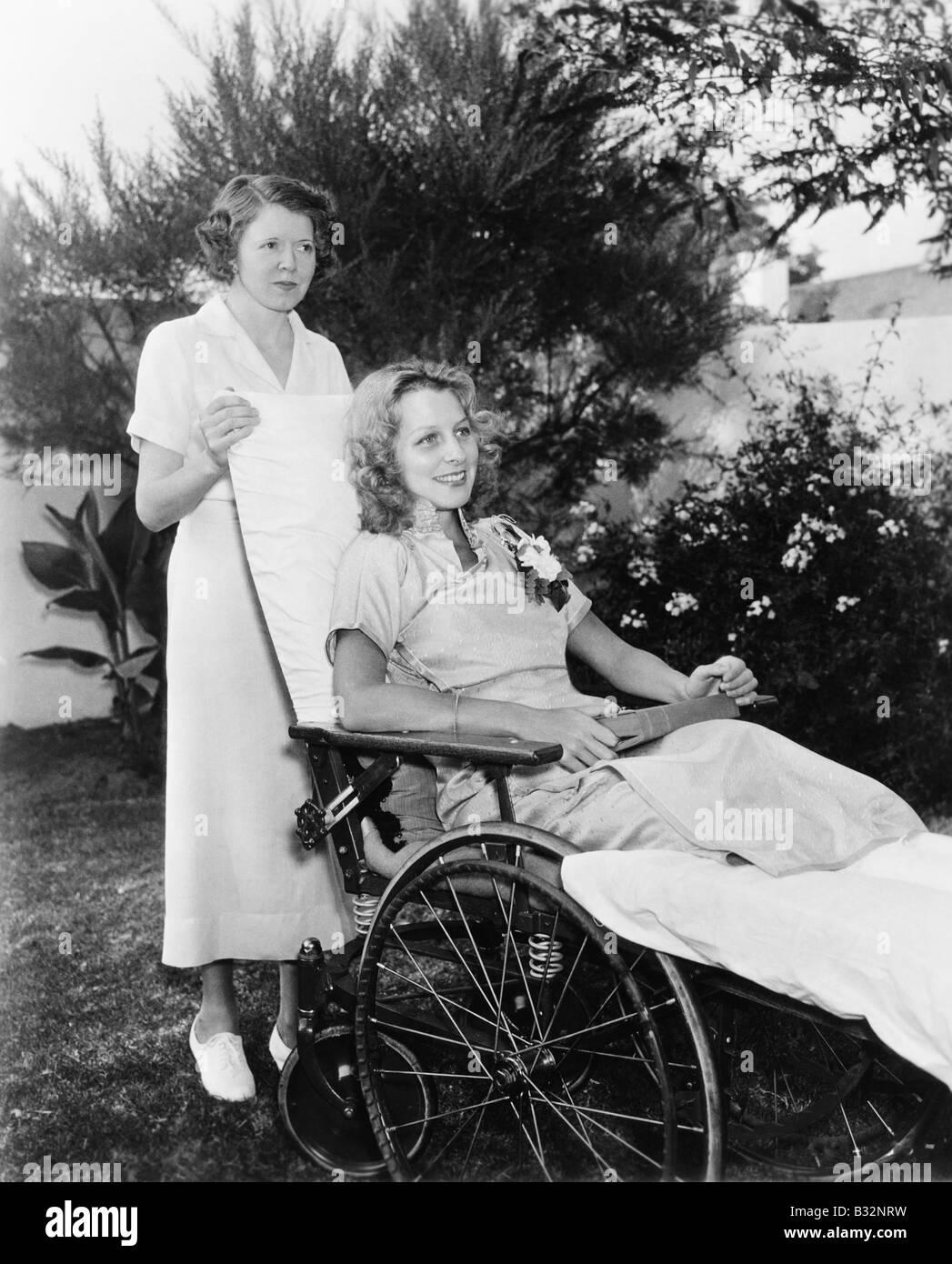 Frau im Rollstuhl mit Krankenschwester Stockbild