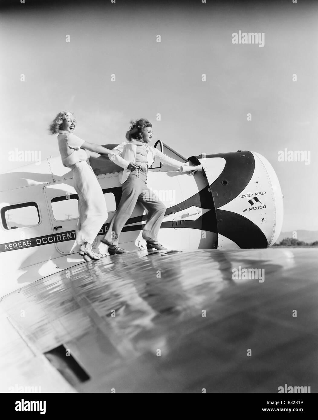 Zwei Frauen zu Fuß auf dem Flügel eines Flugzeuges Stockbild