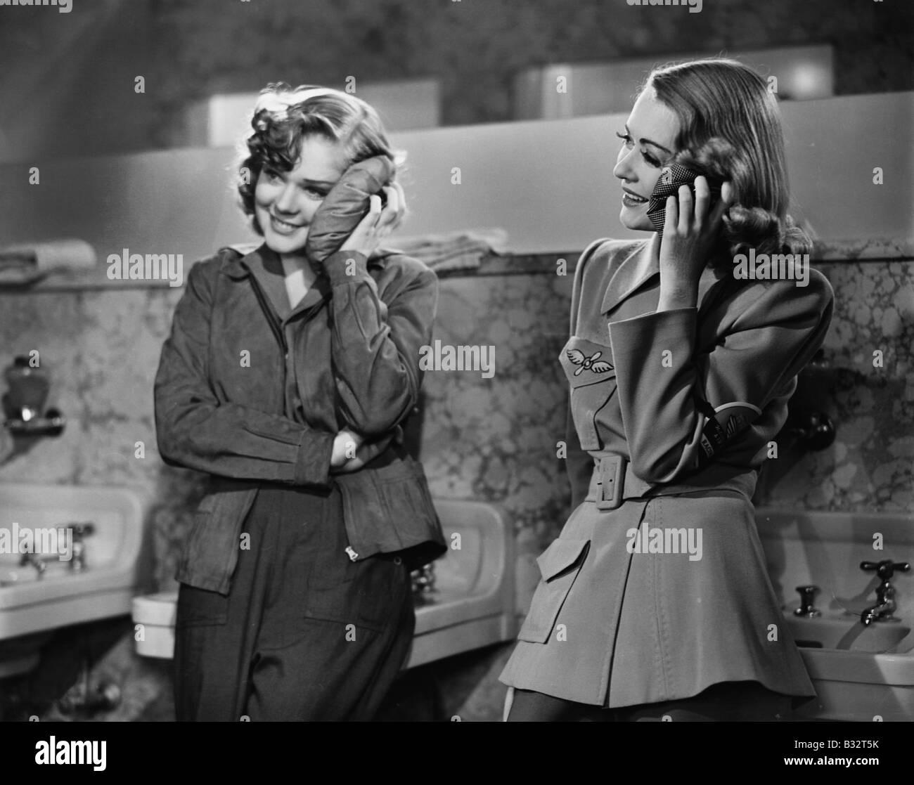 Zwei junge Frauen ein Waschbecken gelehnt und Anwendung von Eispackungen auf ihren Gesichtern Stockbild