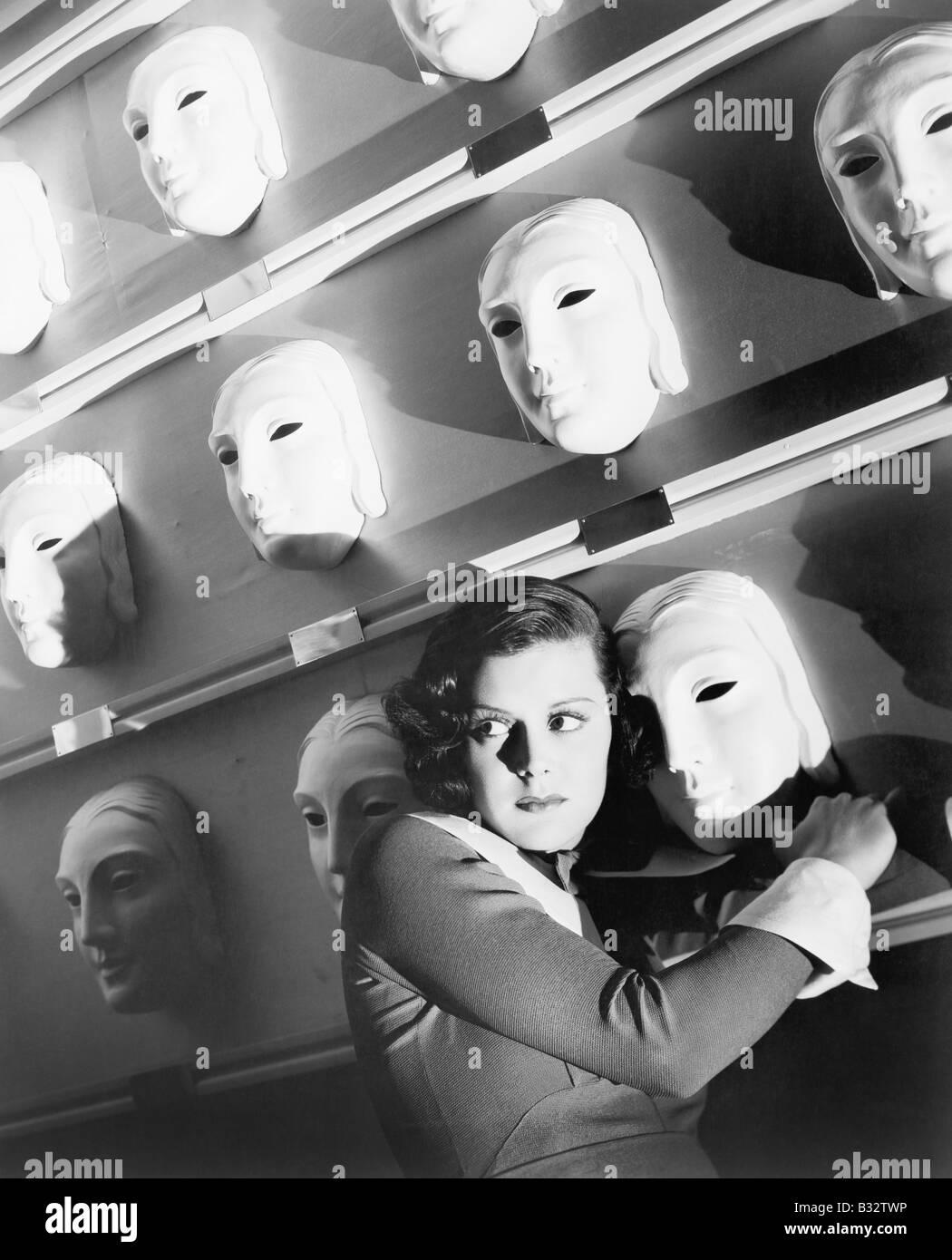 Frau, die Angst hielt sich an eine Maske an der Wand der Masken Stockfoto