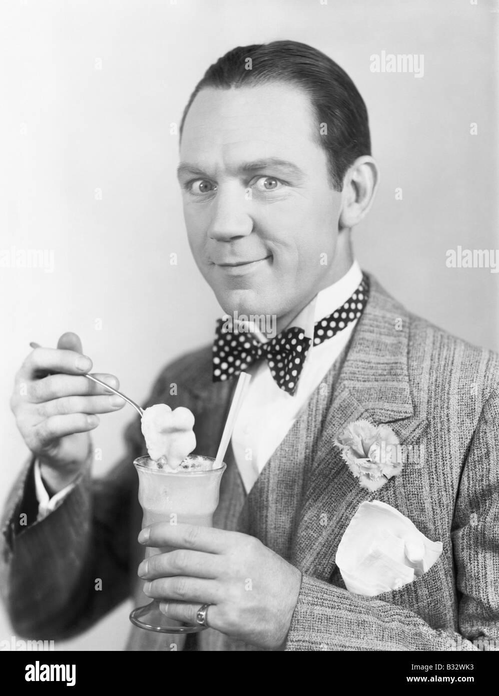 Mann isst ein Eis aus einem Glas mit einem Strohhalm Stockbild