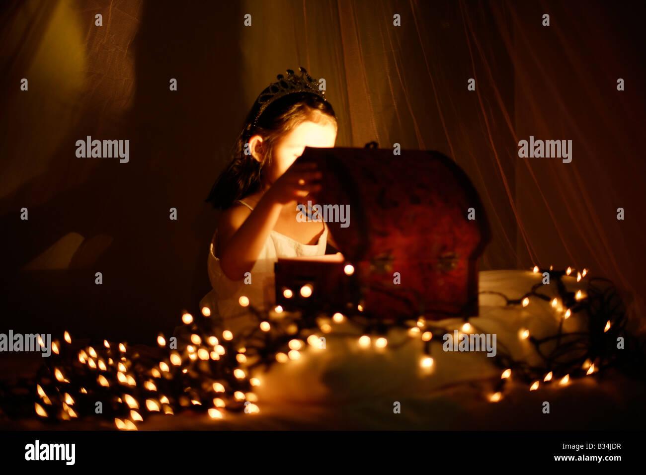 Der magische Schatz Brust fünf Jahre altes Mädchen sitzt auf dem Bett mit Baldachin und öffnet sich Stockbild