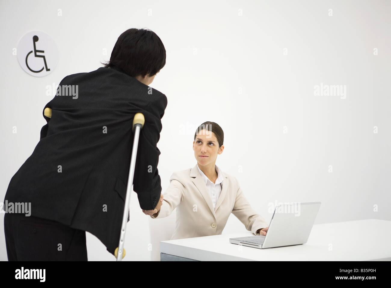 Berufstätige Frau Händeschütteln mit Mann auf Krücken Stockfoto