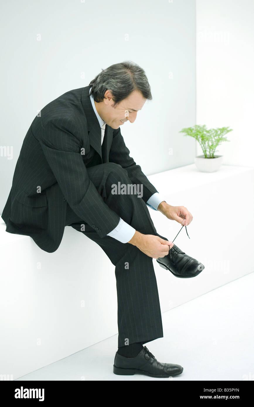 Geschäftsmann sitzt auf der Kante, Kopplung Schuh Stockbild