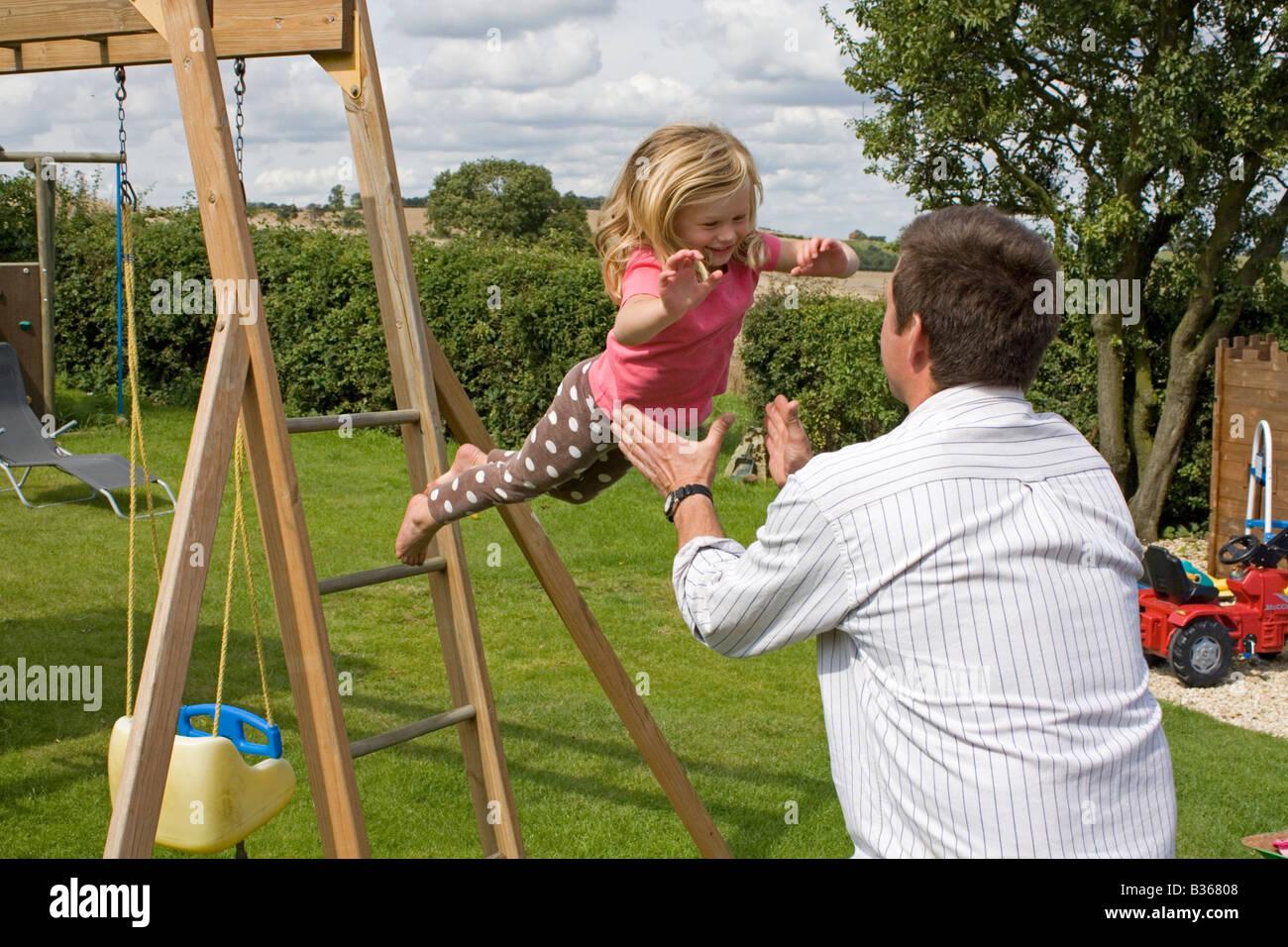Klettergerüst English : Kind vom klettergerüst in väter arme springen stockfoto bild