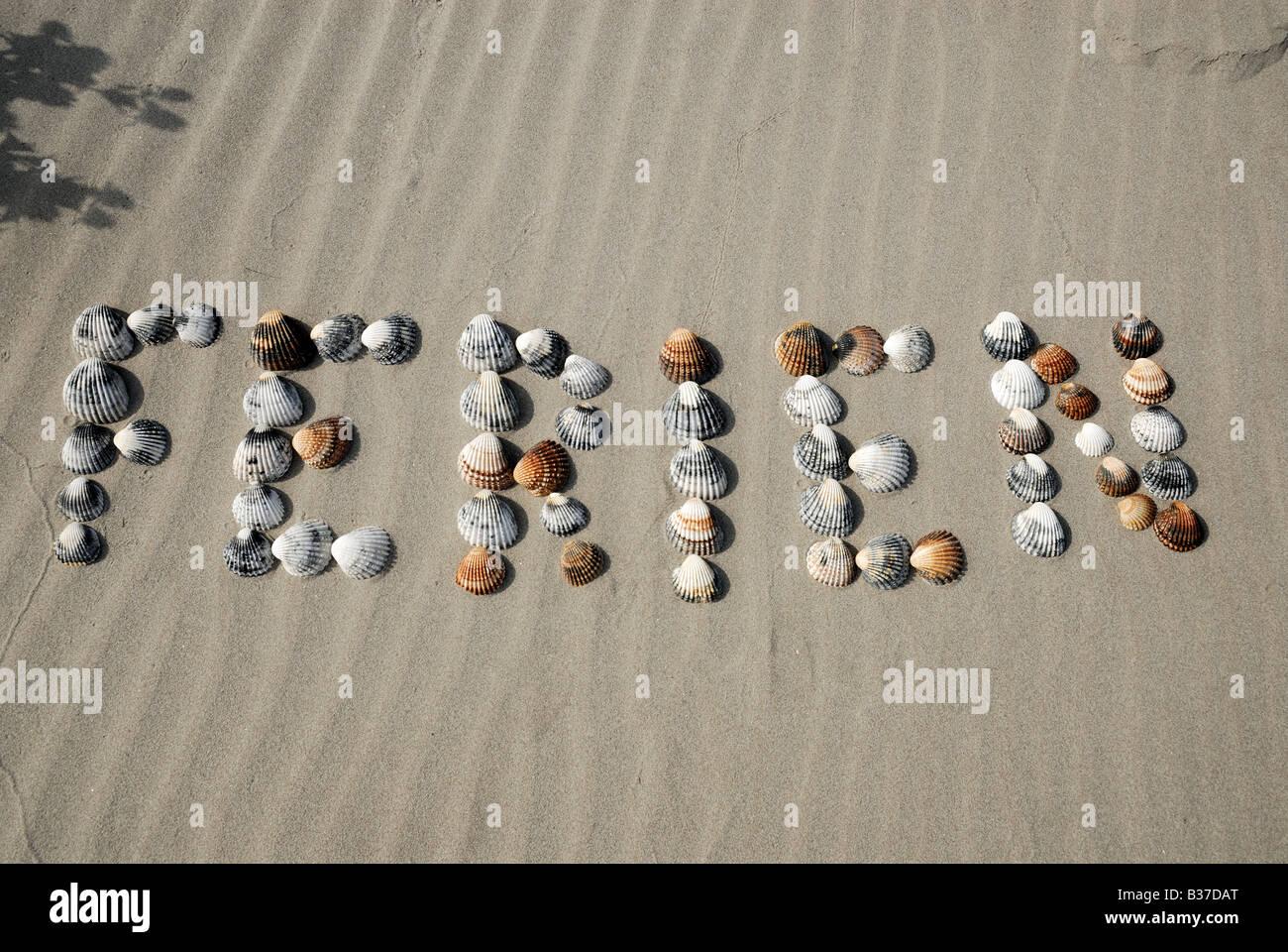 Das Wort Ferien - Deutsch für Urlaub, gemacht von Muscheln am Strand Stockbild