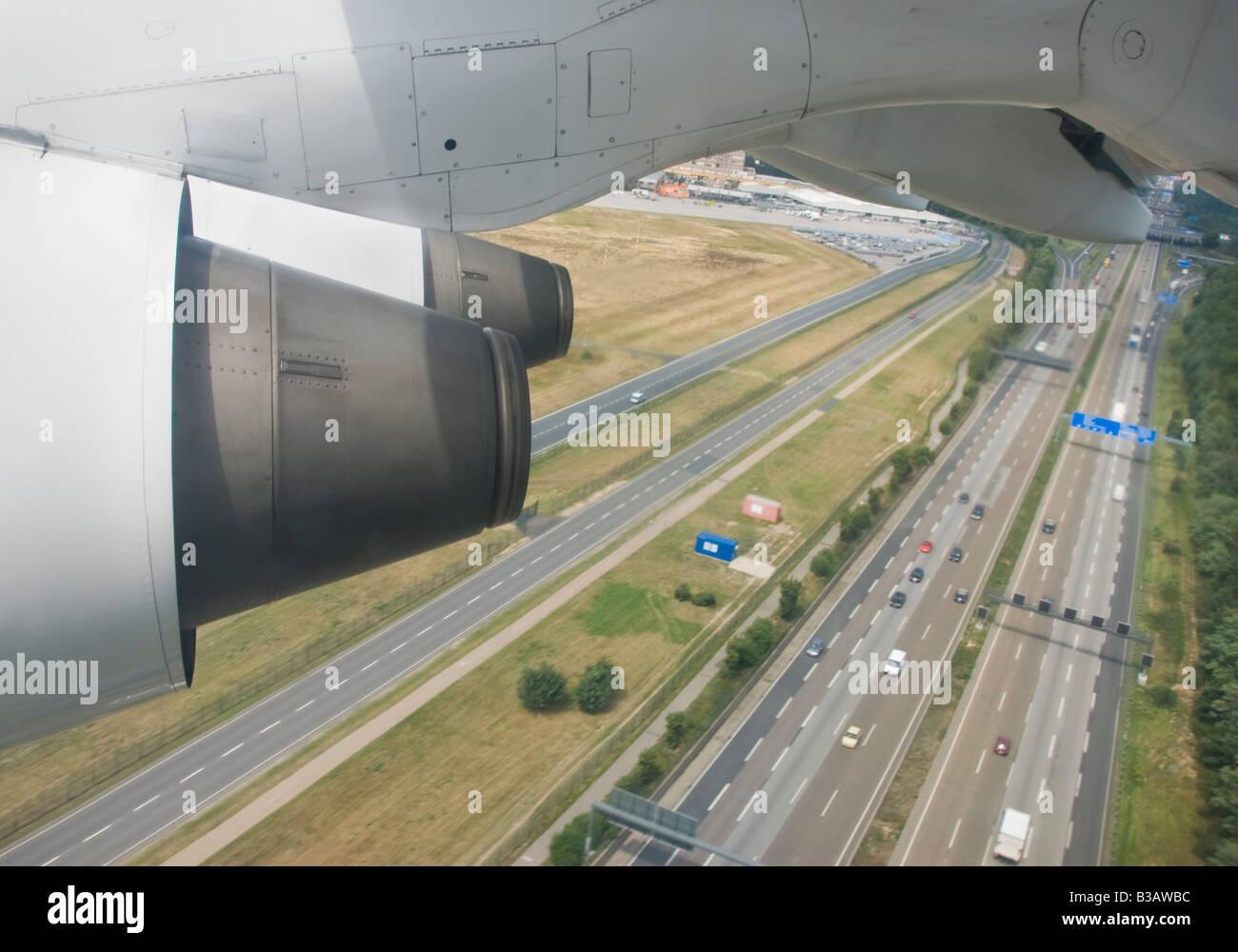 Ein Flugzeug fliegt über eine Autobahn Stockbild