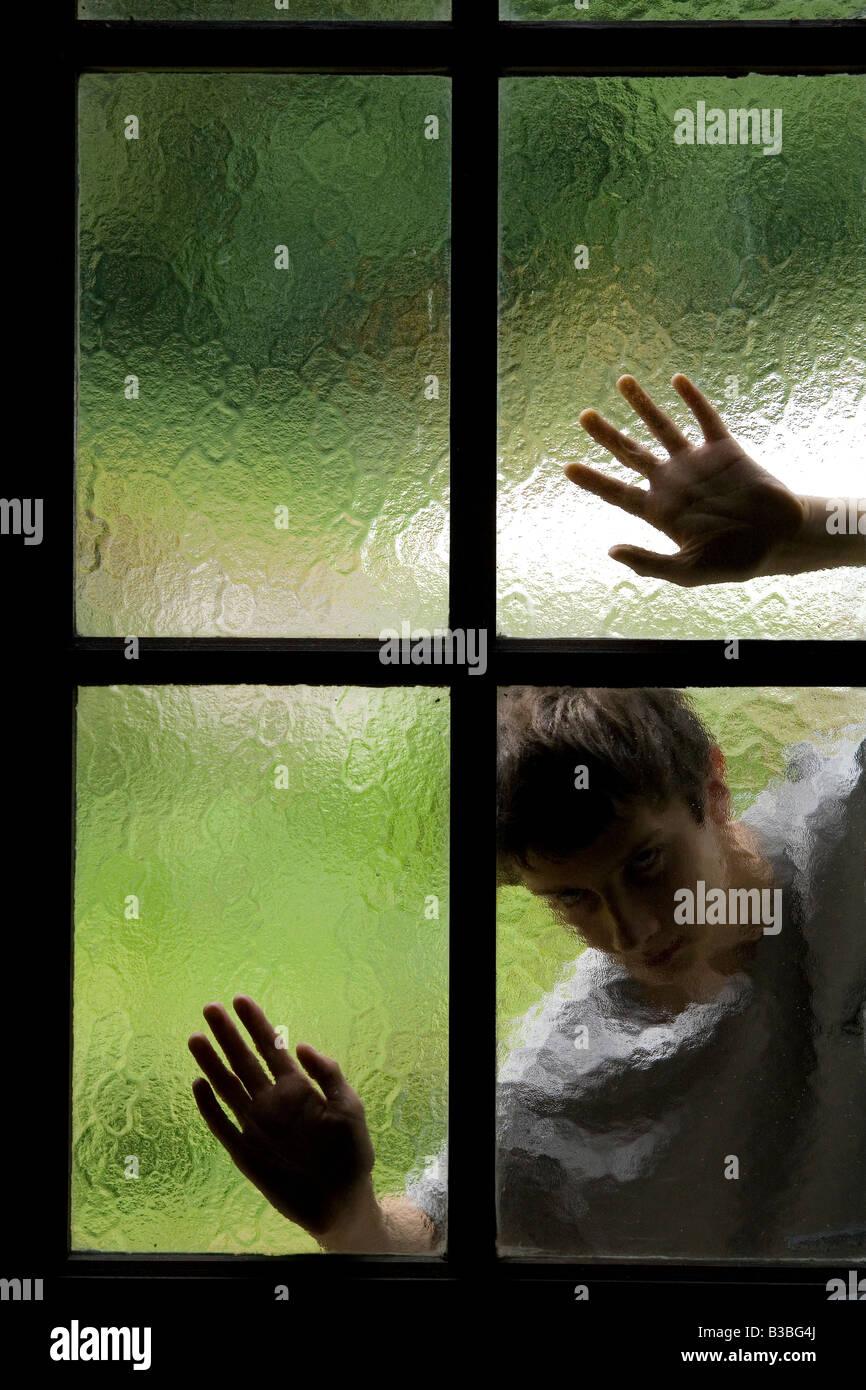 Silhouette der Person hinter Glasfenster mit Hände auf Glasscheiben Stockbild