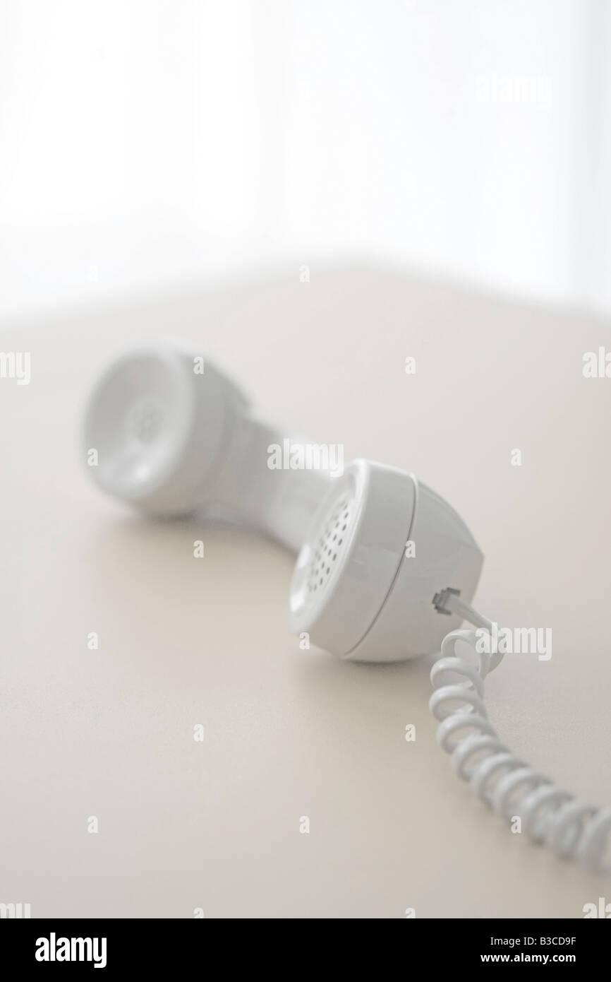 Telefonhörer abgehoben auf Tisch Stockbild