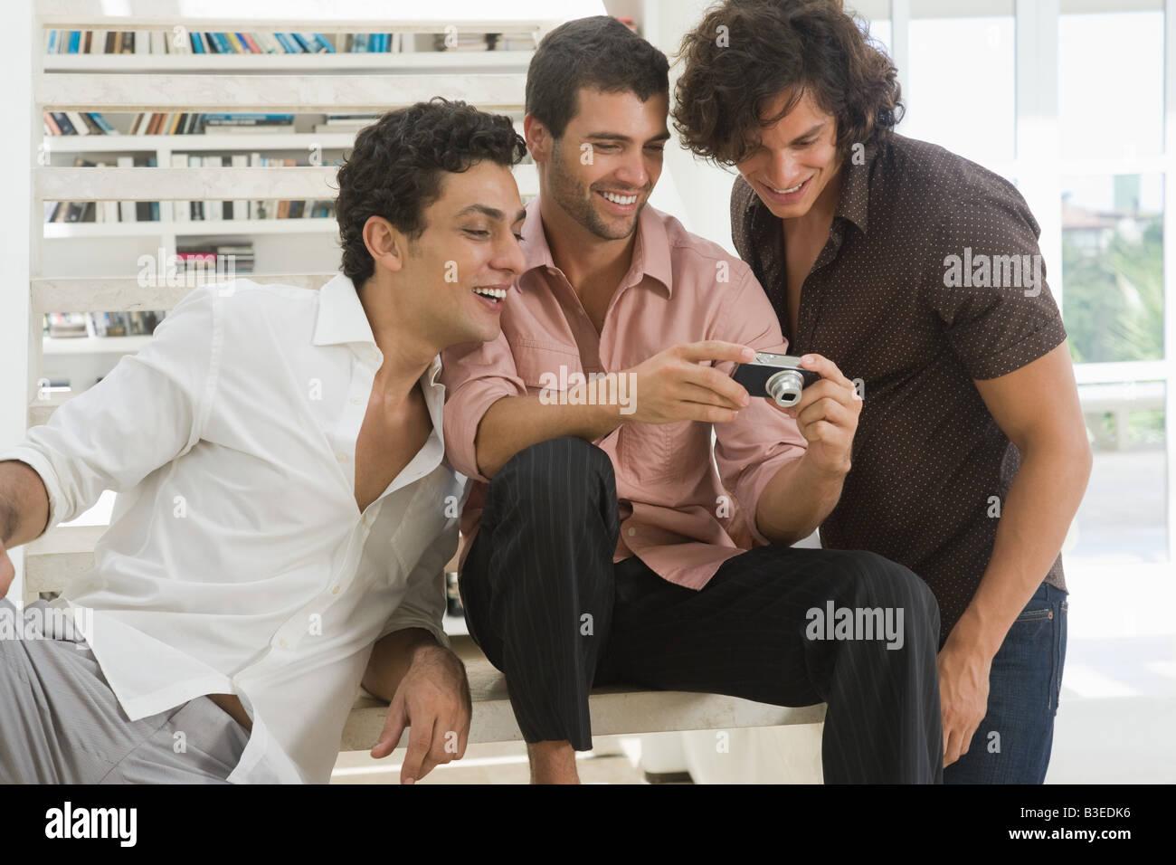 Männer betrachten von Fotos auf einer Kamera Stockbild