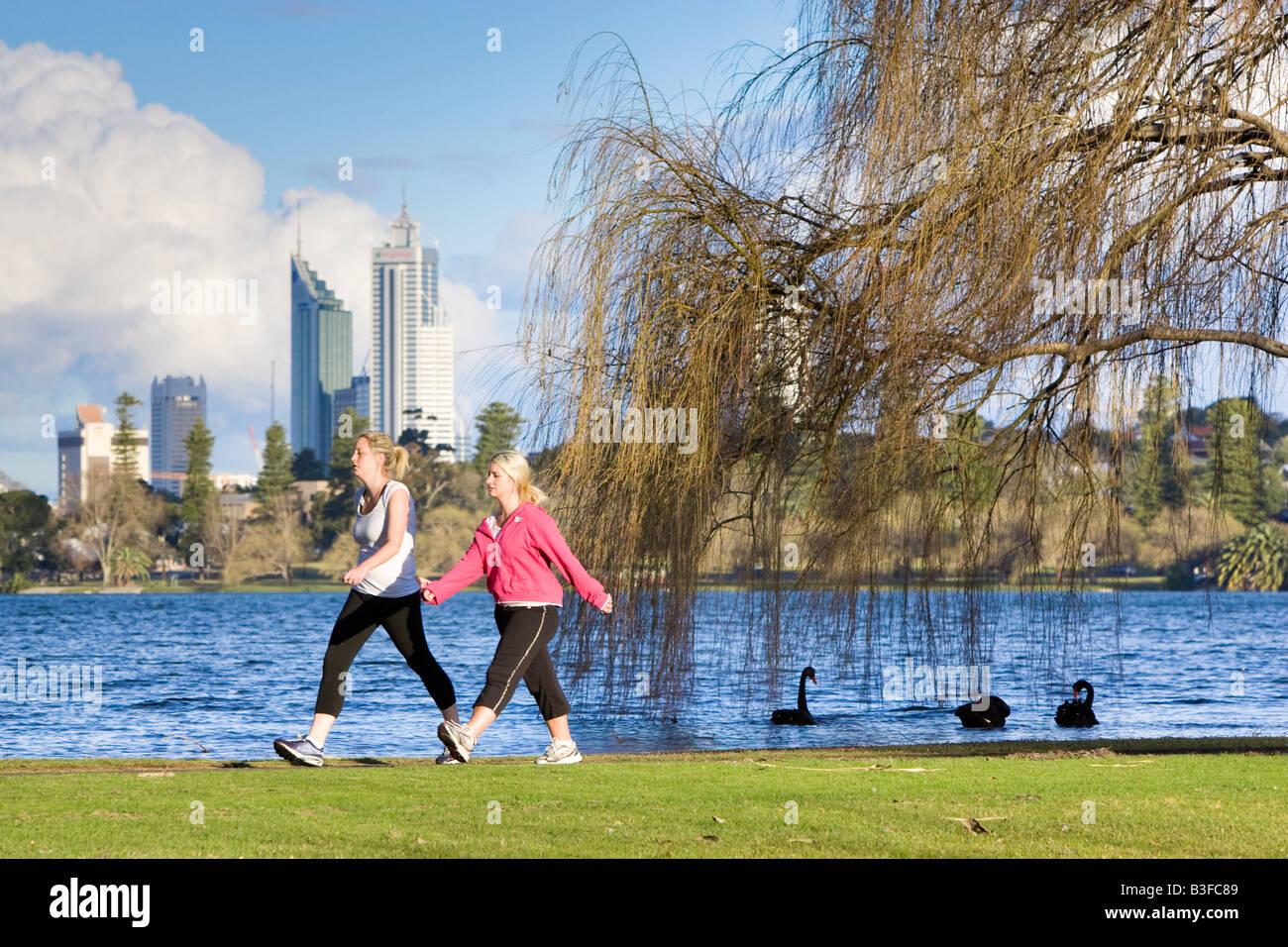 Zwei Frauen trainieren in einem Park mit Wolkenkratzern in der Ferne. Lake Monger, Perth, Western Australia, Australia Stockfoto
