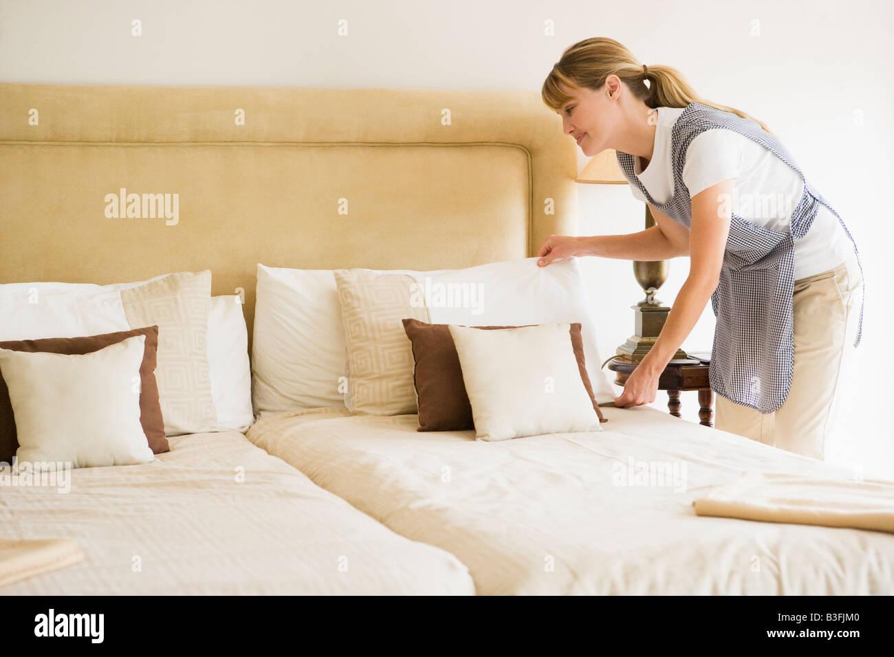 zimmermädchen im hotel zimmer lächelnd bett machen stockfoto, bild