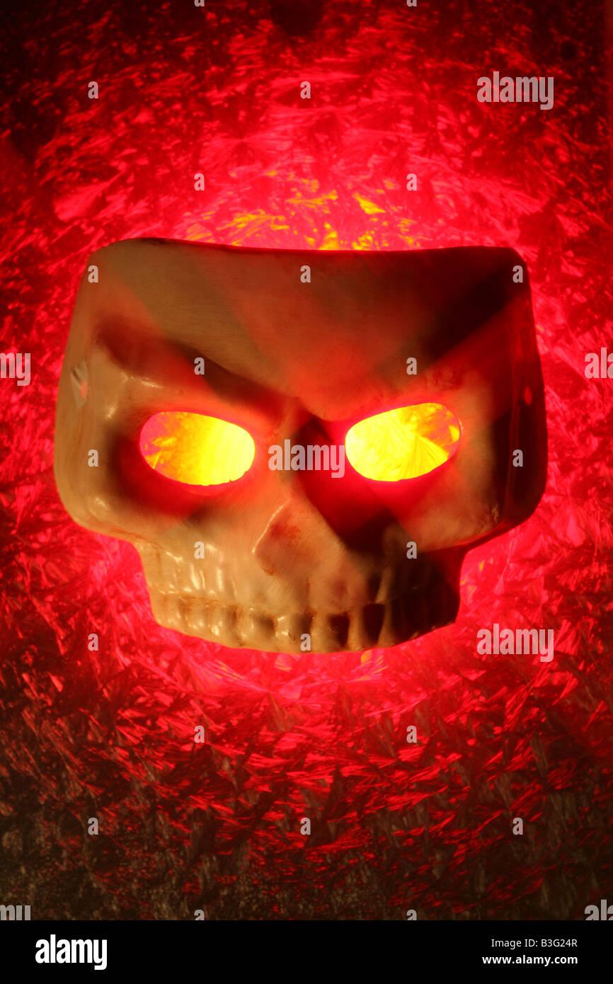 ein Schädel-Maske mit leuchtenden gelben Augen und roten leuchtenden Hintergrund Stockbild