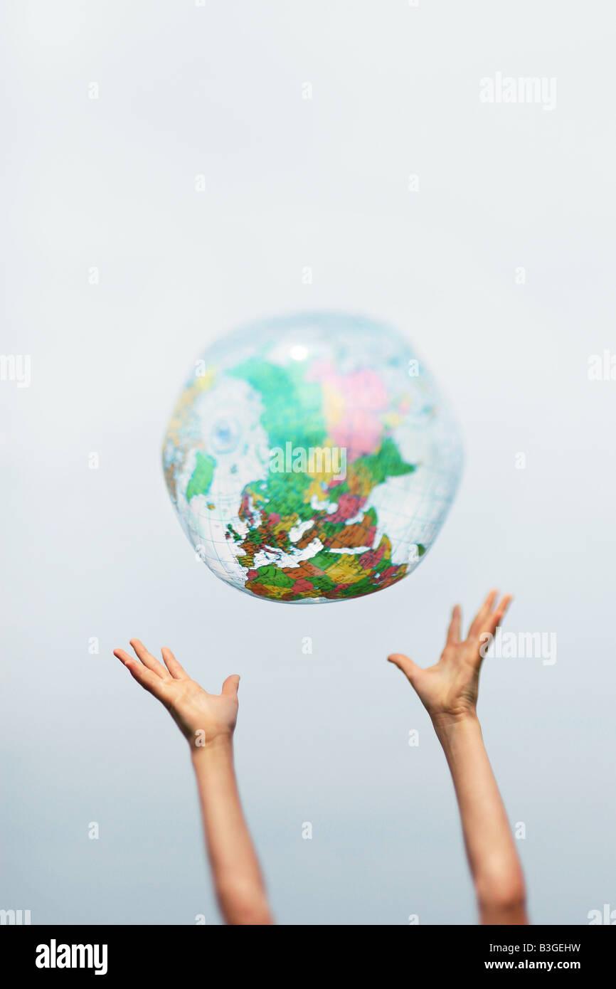 die Hände fangen eine aufblasbare Globus Stockbild