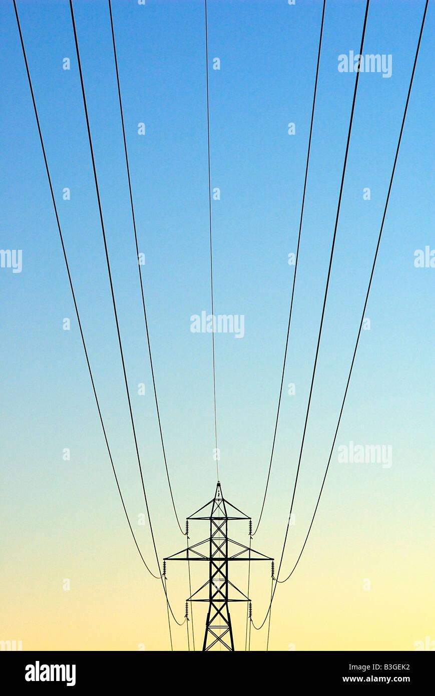 Elektrische Turm und Stromleitungen im Sonnenaufgang Stockbild