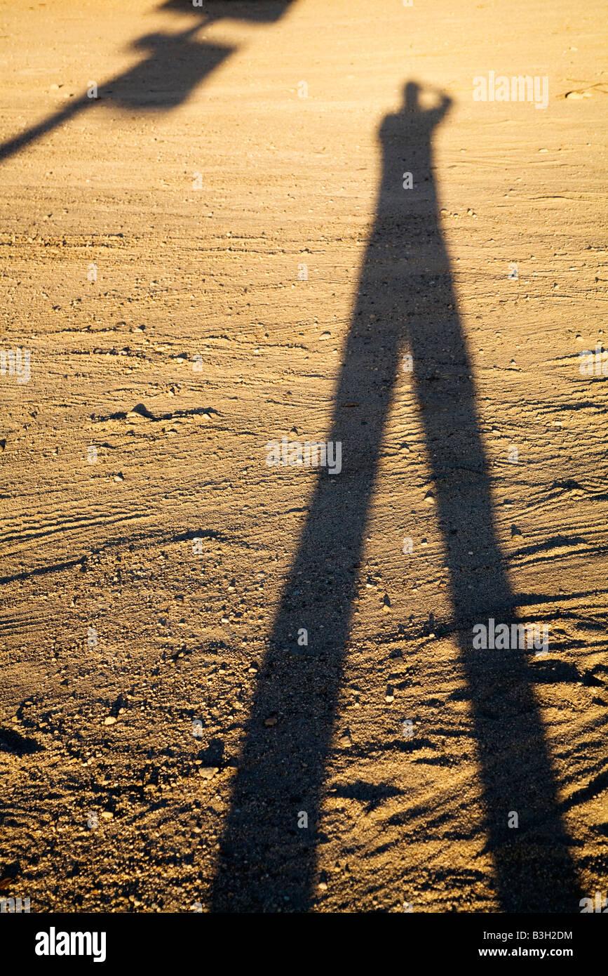 Schatten des Mannes auf Schmutz bei Sonnenuntergang Stockbild