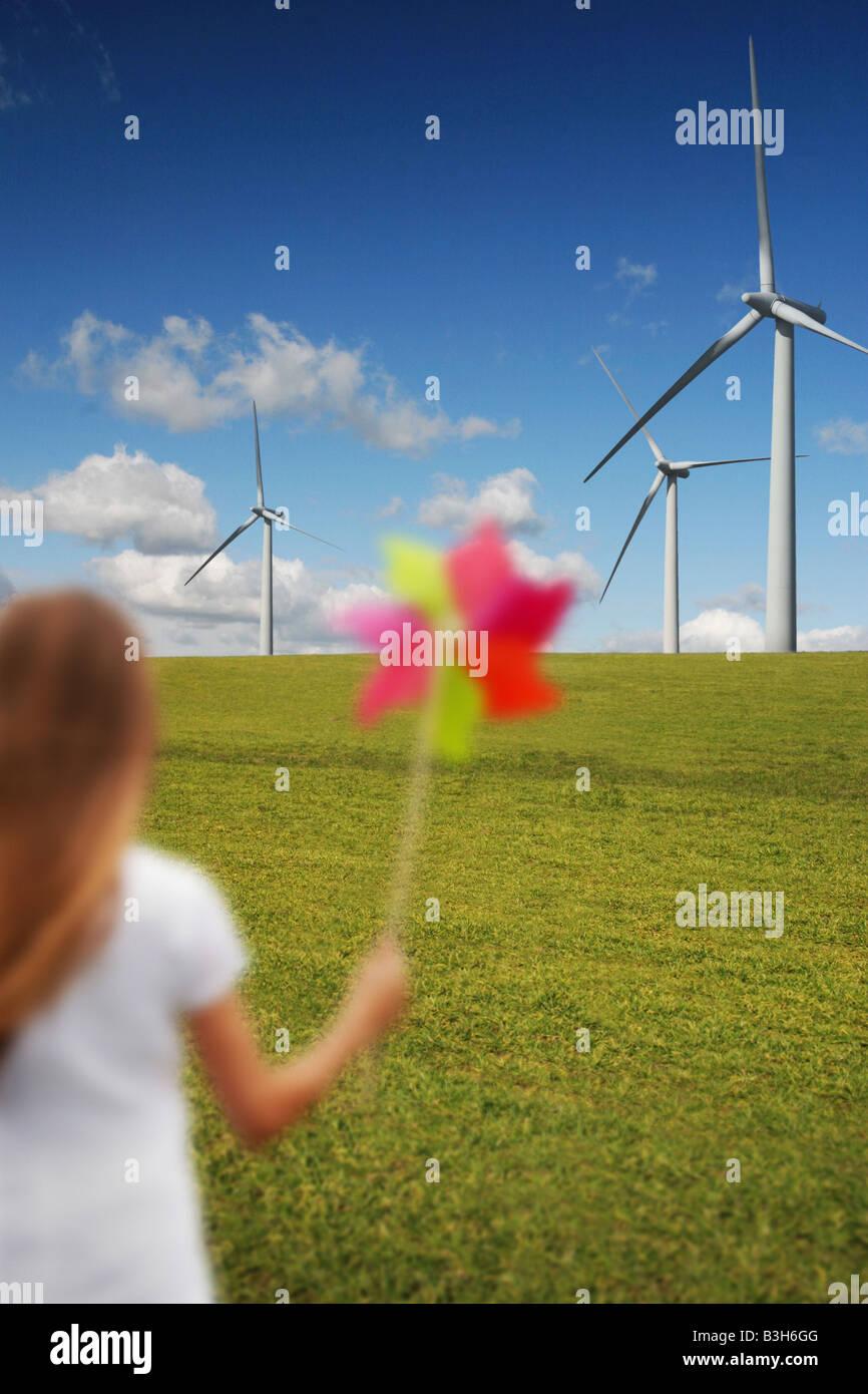 Mädchen mit Windmühle vor Windturbinen Stockbild