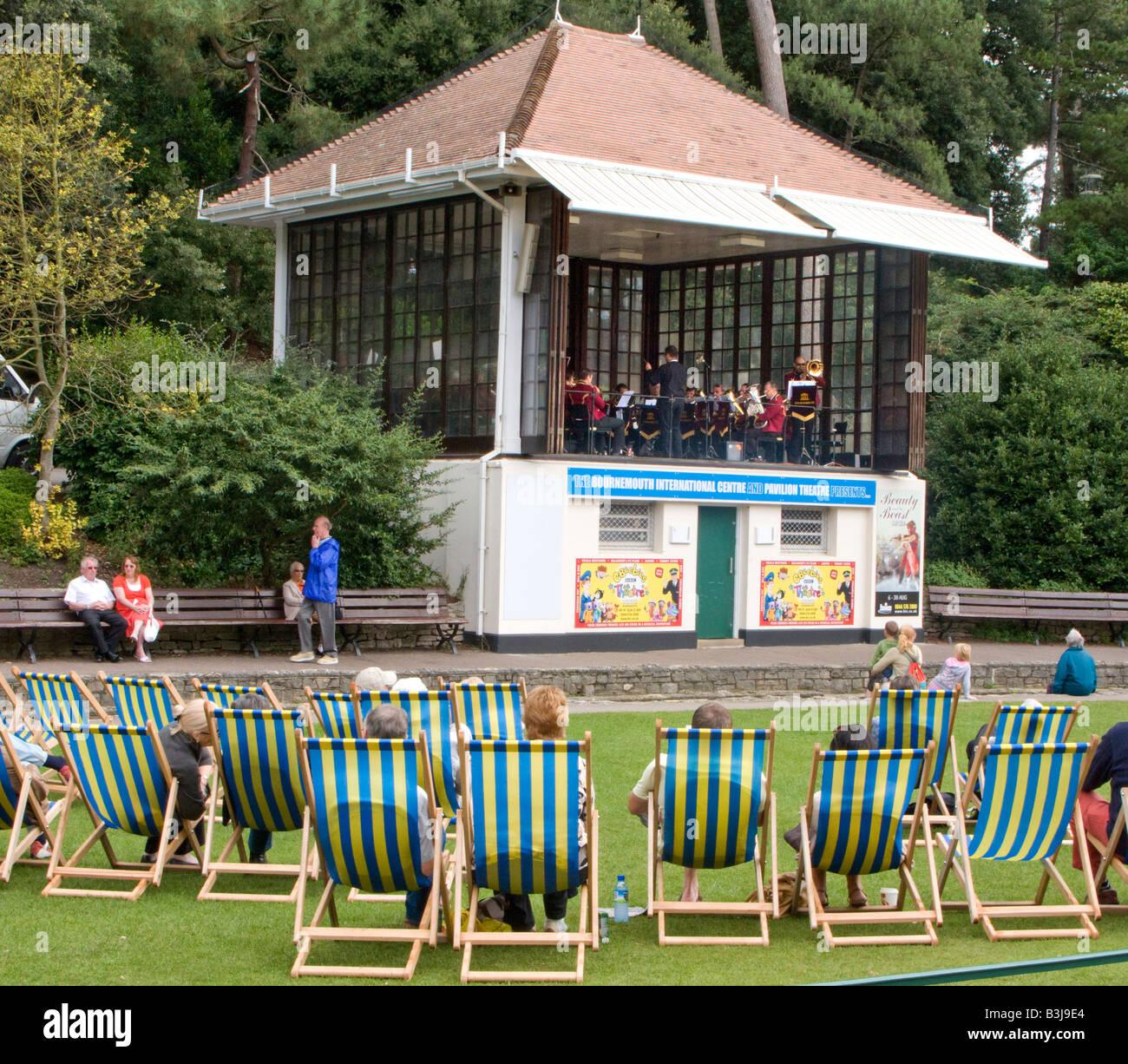 Menschen in Liegestühlen, die gerade ein Konzert in Bournemouth Gardens, Dorset, Großbritannien Stockbild