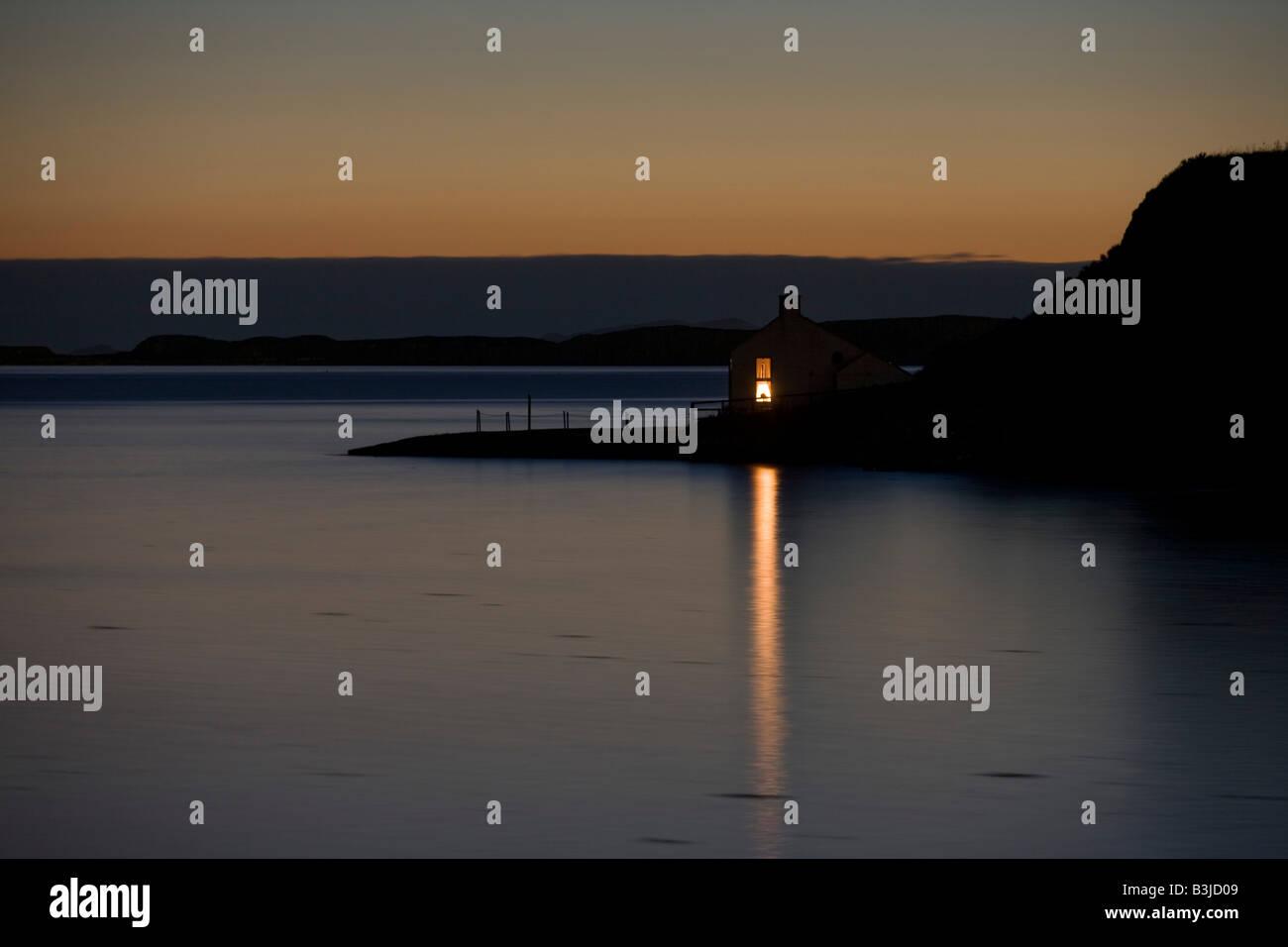 Einem hellen Fensterlicht strahlt über die noch Loch Bucht von einem abgelegenen Haus in Stein, Waternish Punkt Stockbild