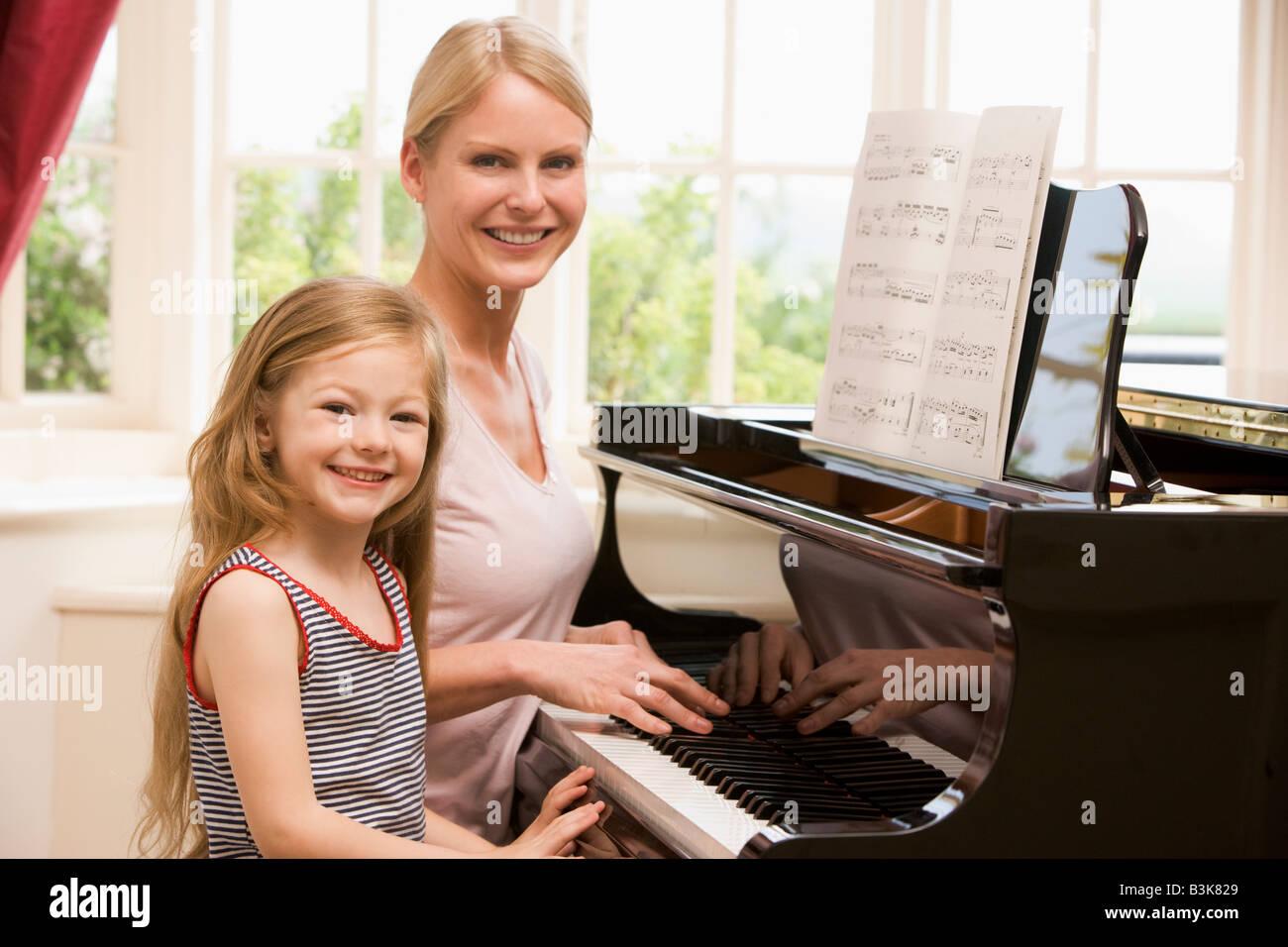 Frau und junge Mädchen spielt Klavier und lächelnd Stockbild