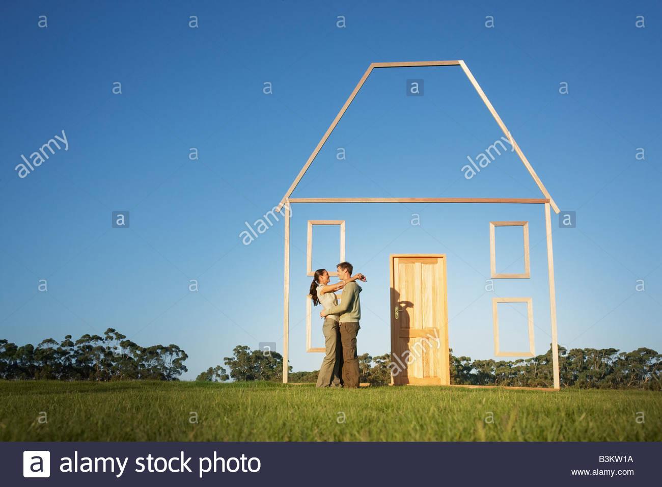 Paar umarmt neben vertikale Haus Gliederung Stockbild