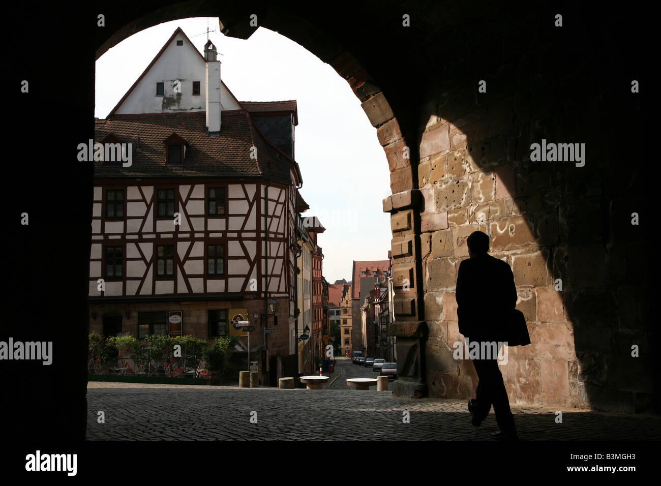 Silhouette Mann zu Fuß durch das mittelalterliche Tor Tiergartnertor, Albrecht Durer Haus in Nürnberg, Stockbild