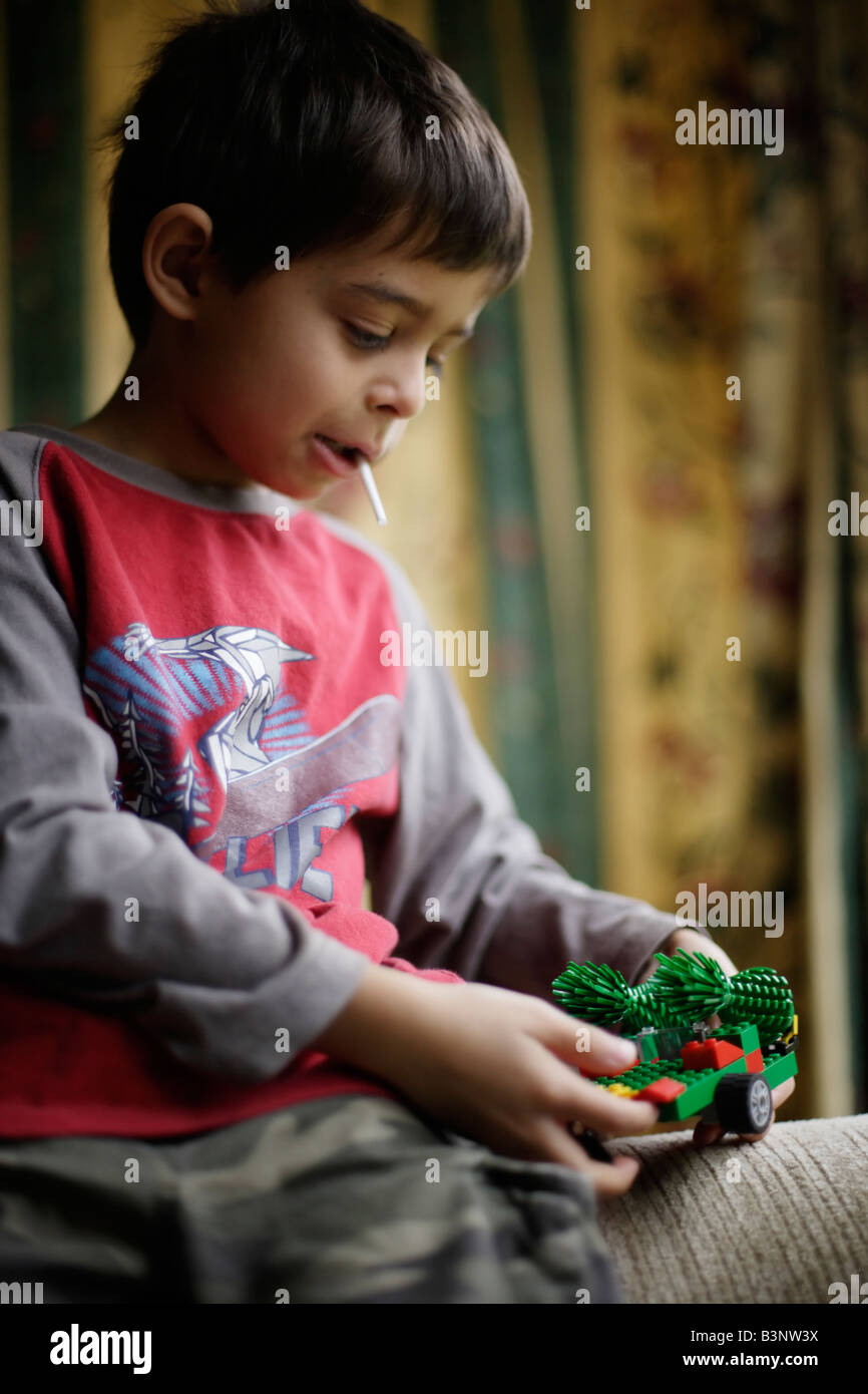 Jungen im Alter von sechs saugt Lollipop beim Bau Spielzeug mit Plastikziegelsteine Stockbild