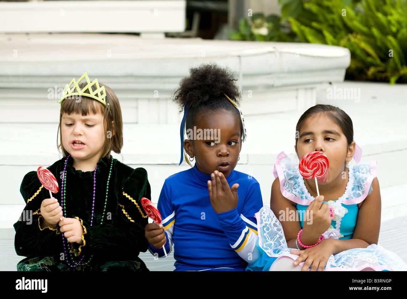 Kleine Mädchen, gekleidet in Halloween-Kostümen genießen ihr Lutscher, wie man erwischt Rothändige Stockbild
