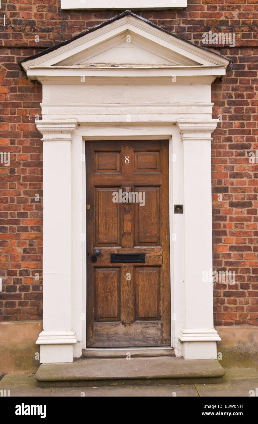 Braune hölzerne Eingangstür mit weißem Rahmen und Giebel auf ...