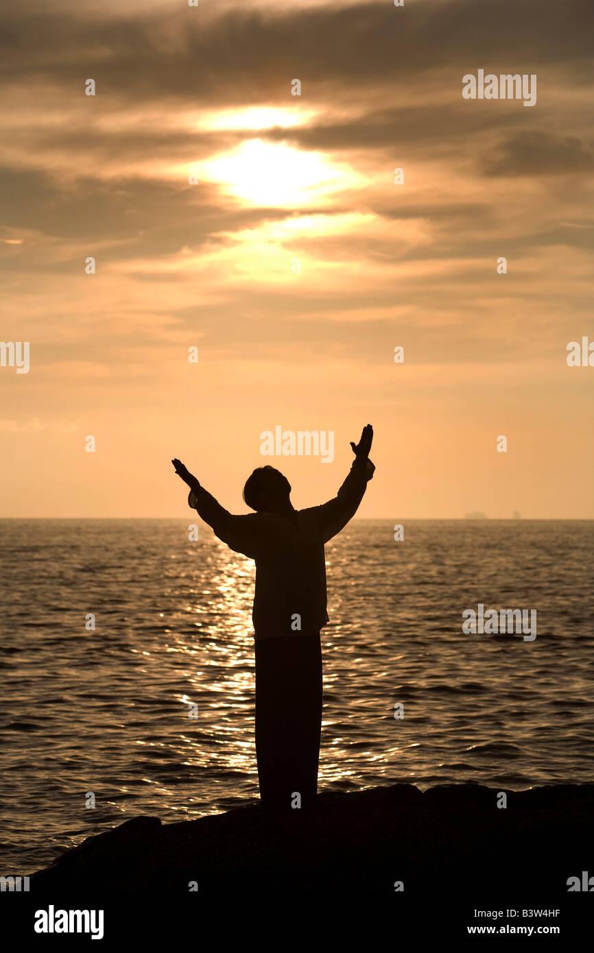 Eine Person mit Armen am Strand bei Sonnenuntergang Stockbild