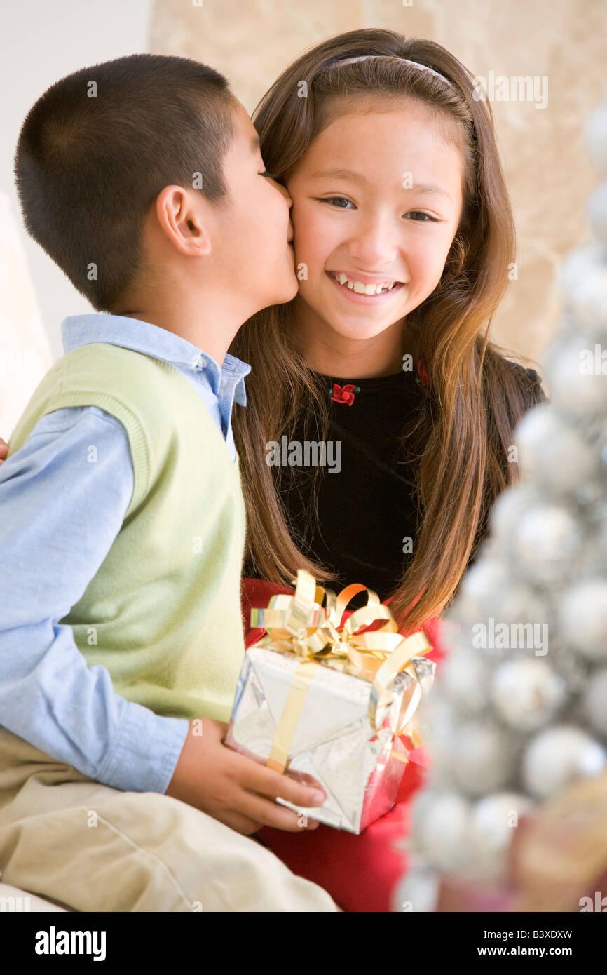 Bruder seine Schwester auf die Wange zu küssen, und halten ein ...