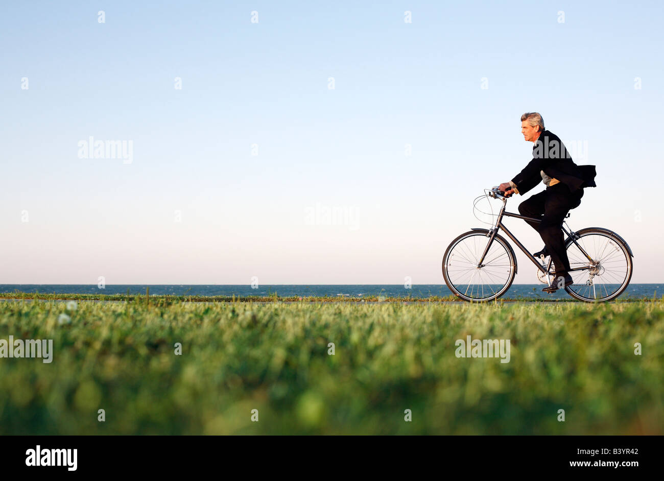 Mann im Anzug fährt Rad entlang Chicago Lakefront in der Abenddämmerung Stockbild