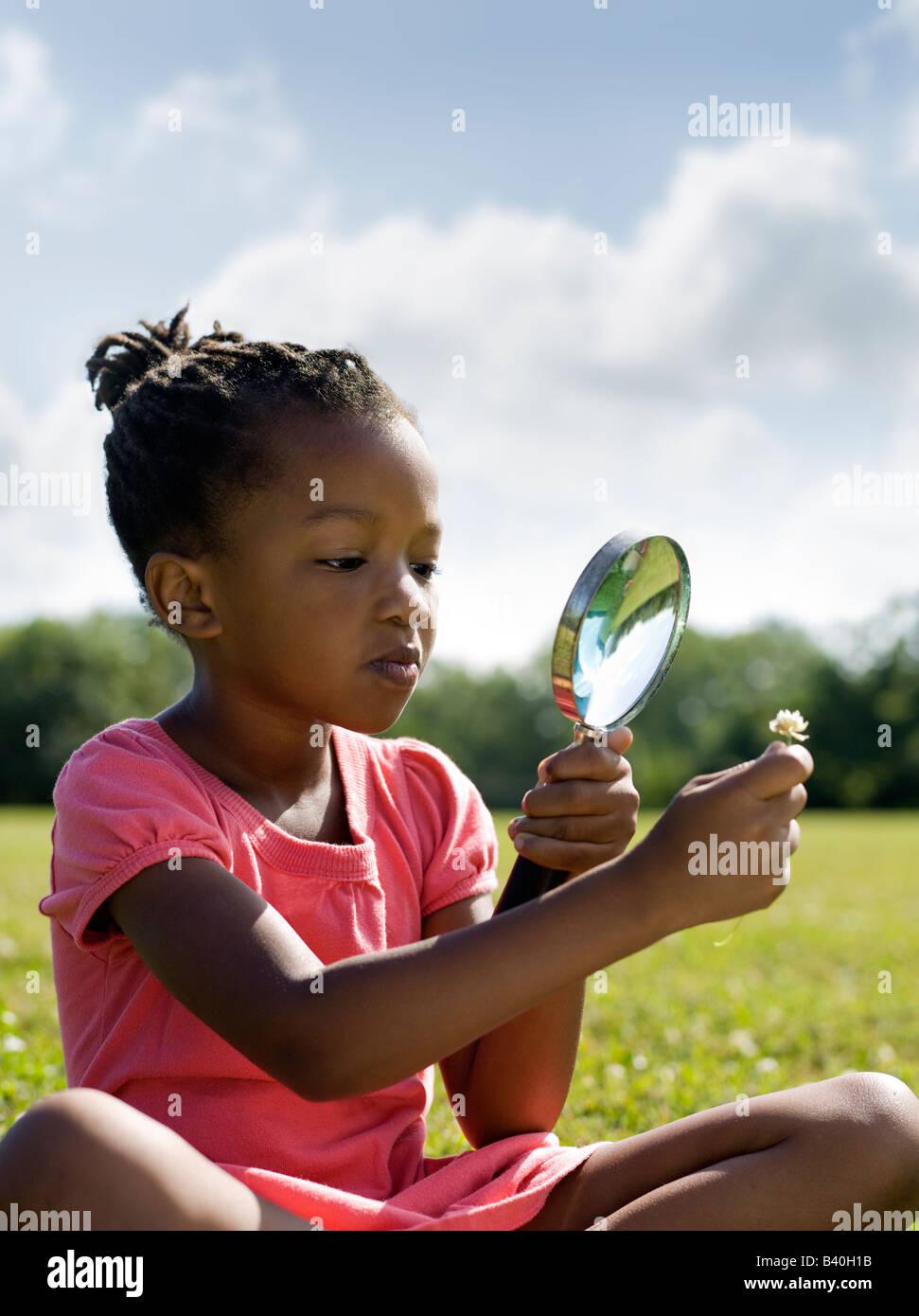 Young African American Mädchen betrachten Blume mit Lupe Chicago Stockbild
