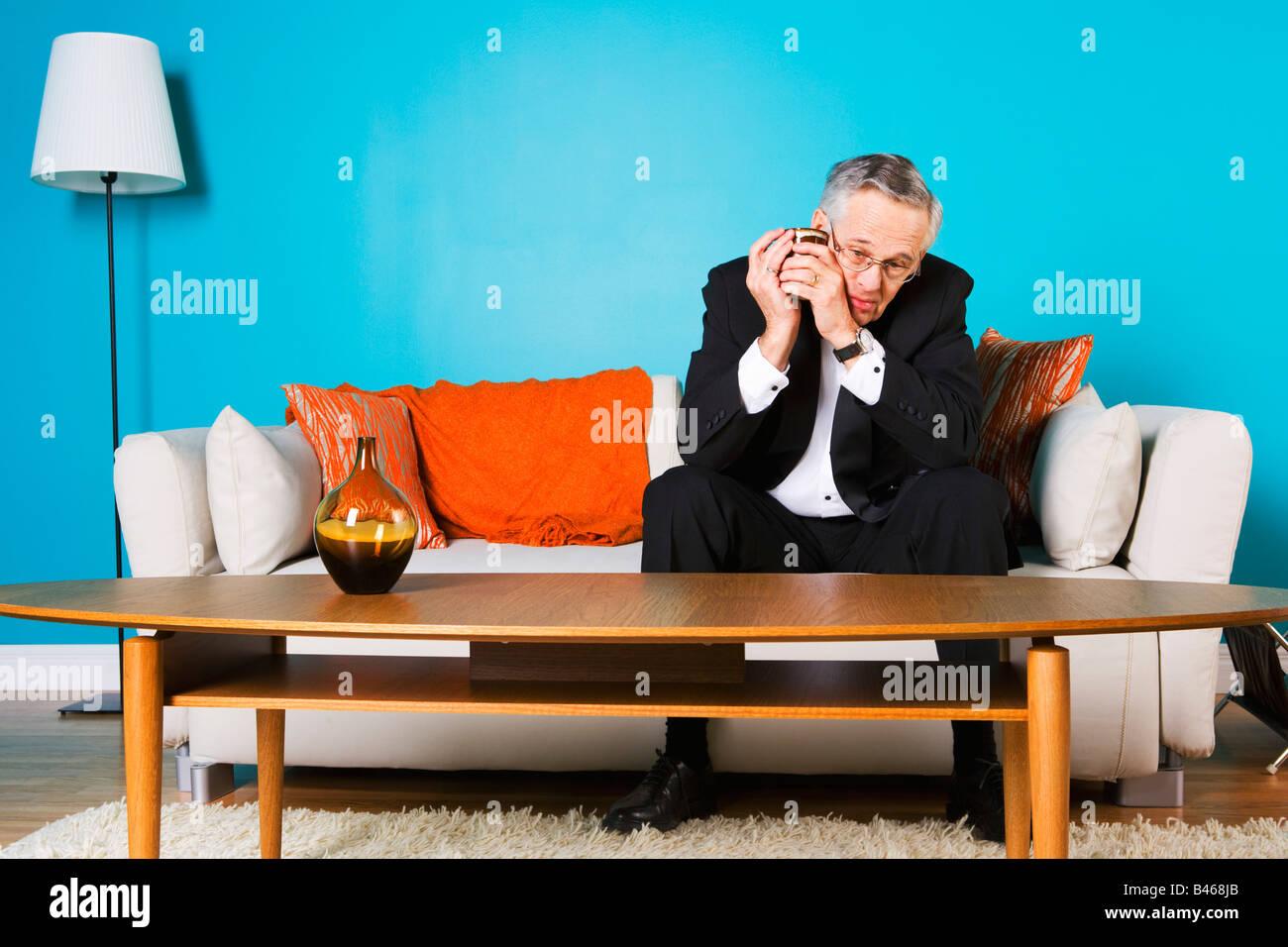 Senior Mann sitzt auf der Couch allein Stockfoto