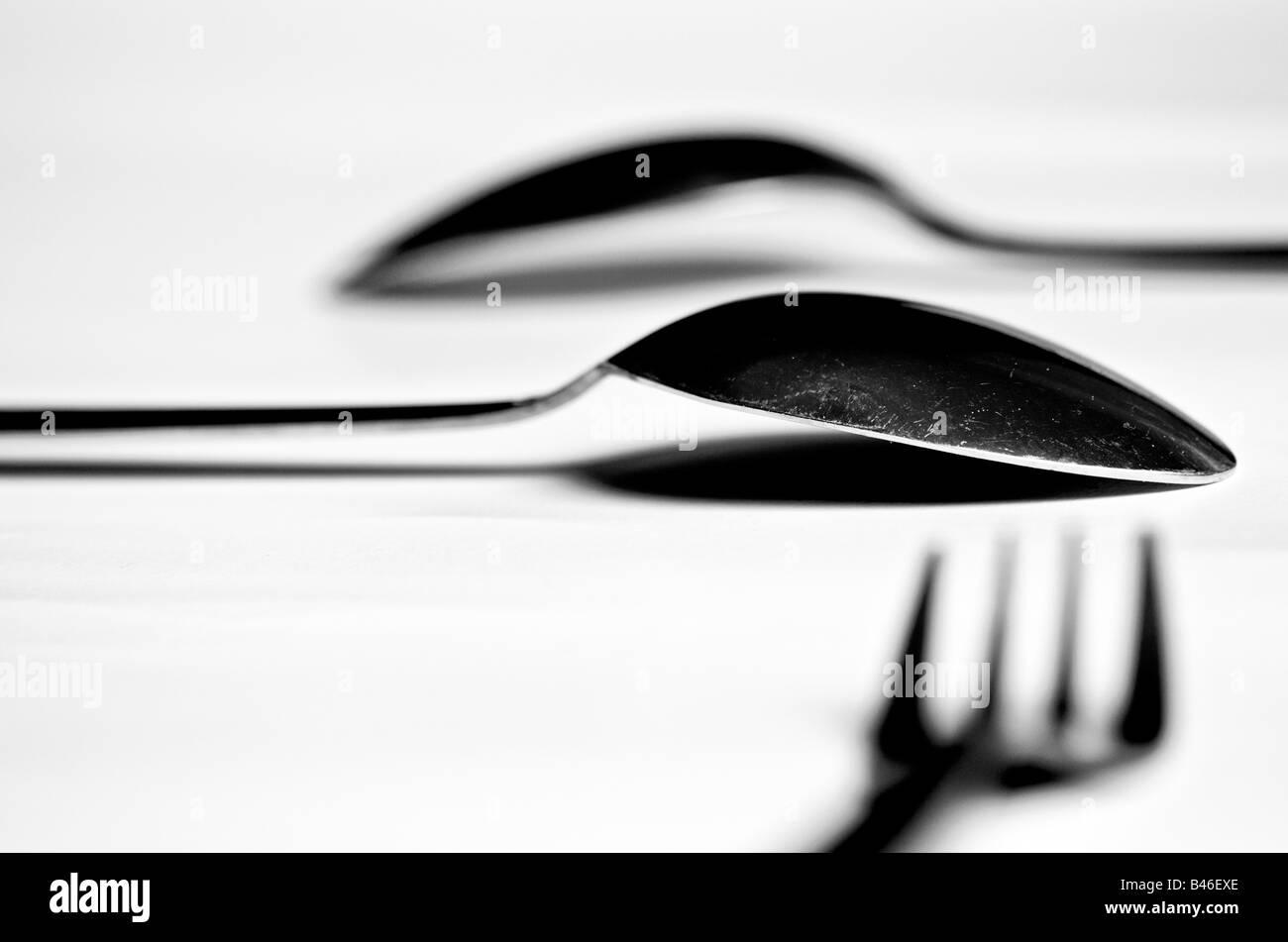 zwei Löffel und einer Gabel auf einem weißen Tisch Stockbild
