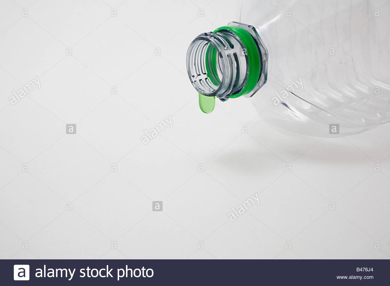 Ein grüner Tropfen auf einer Kunststoff-Flasche Stockbild