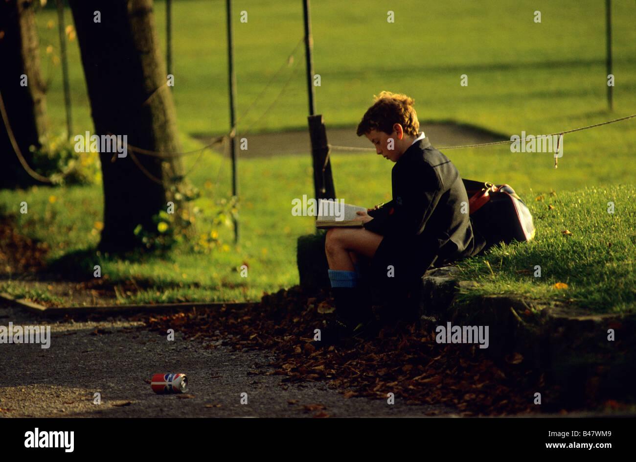 Ein Junge liest ein Buch, während auf einer Mauer sitzend, wie er auf einen Freund in der Manchester Grammatik Stockbild